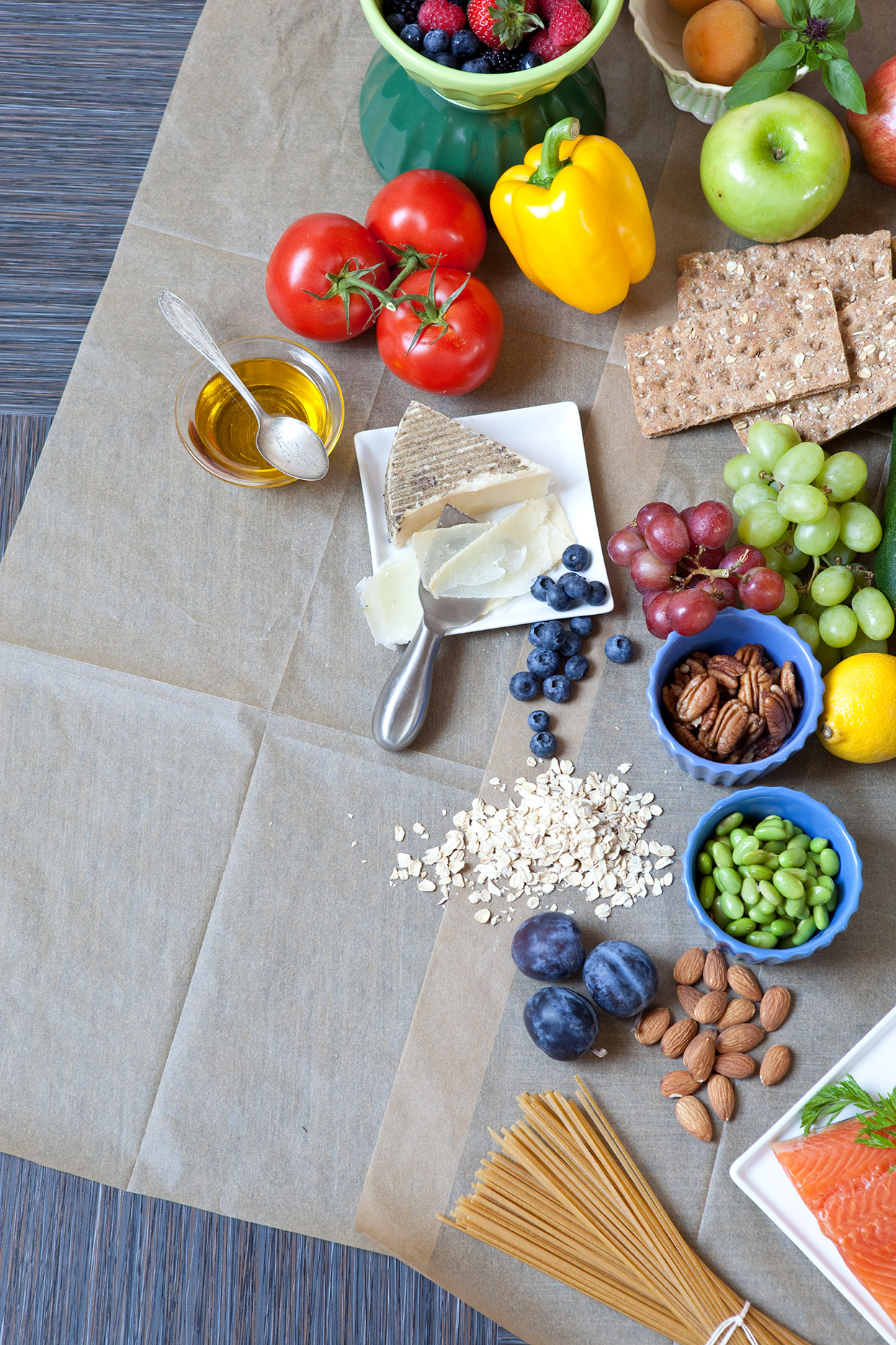 Scattering of healthy ingredients on brown parchment. Ingredients include berries, tomatoes on the vine, bell pepper, apple, wheat cracker, cheese, grapes, pecans, lemon, edamame, oats, plums, almonds, salmon, and whole grain pasta.