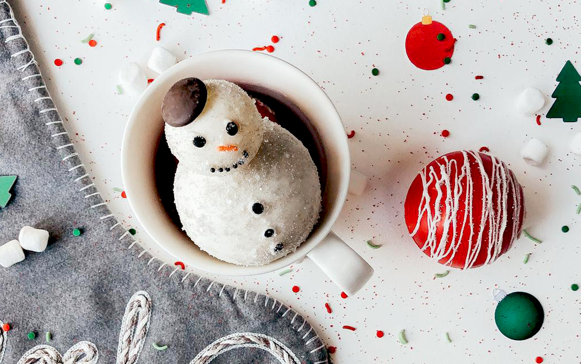 A snowman hot cocoa bomb in a cup of cocoa with holiday decor