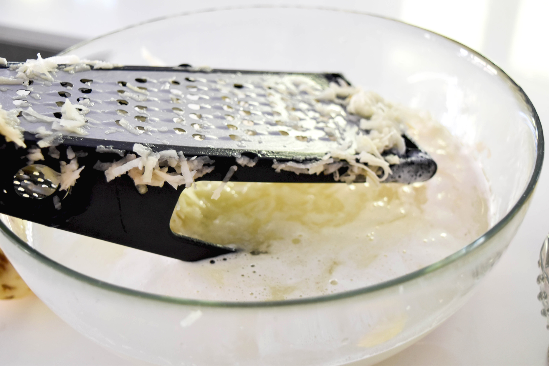 Grater being used on potatoes to make latkes