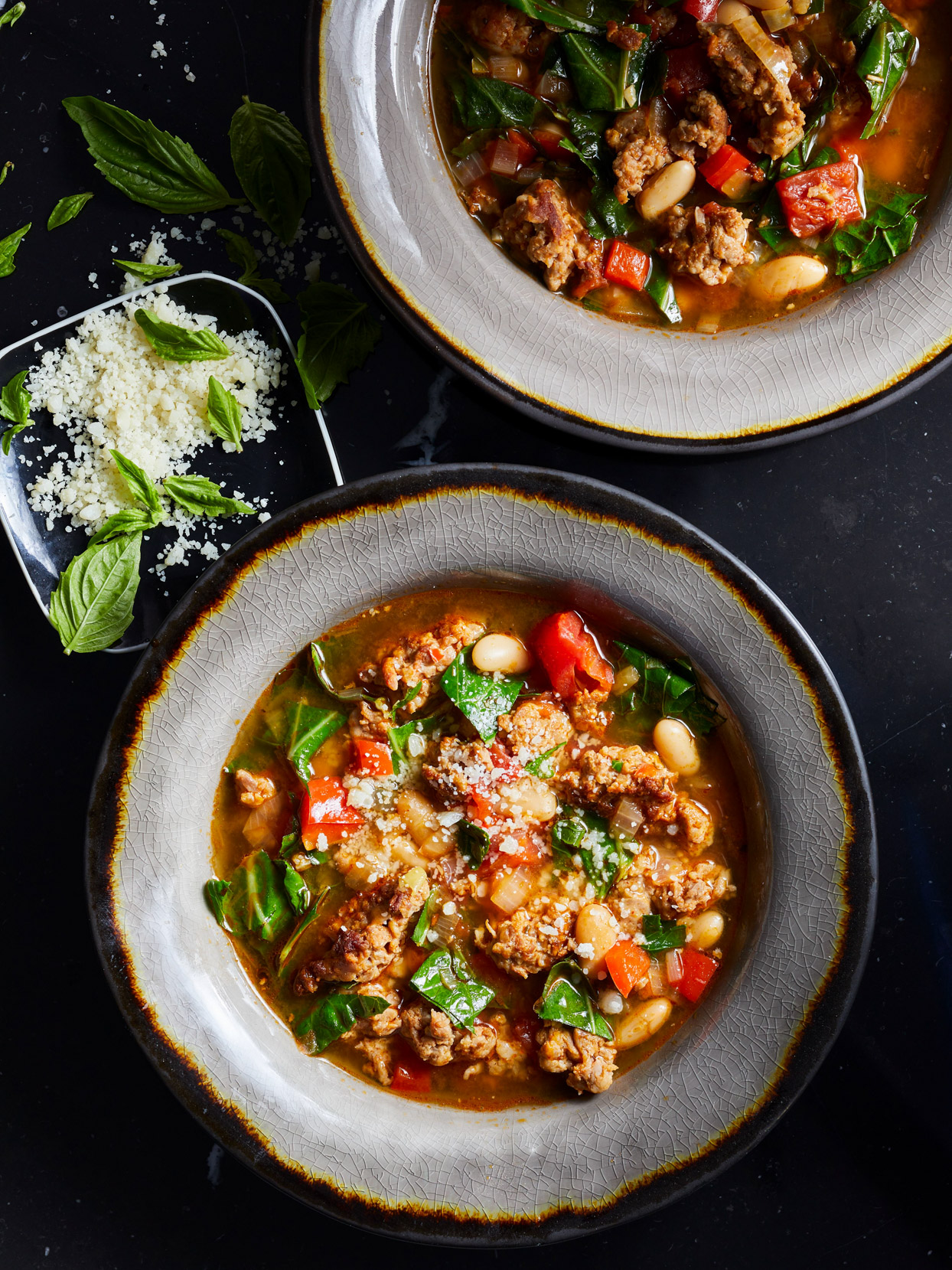 bowls of Spicy Sausage and Collard Soup with parmesan cheese