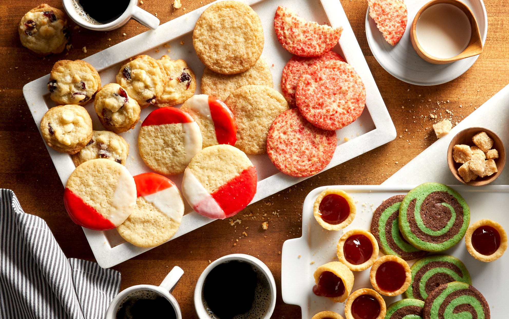 Multiple types of cookies on a wooden surface with coffee