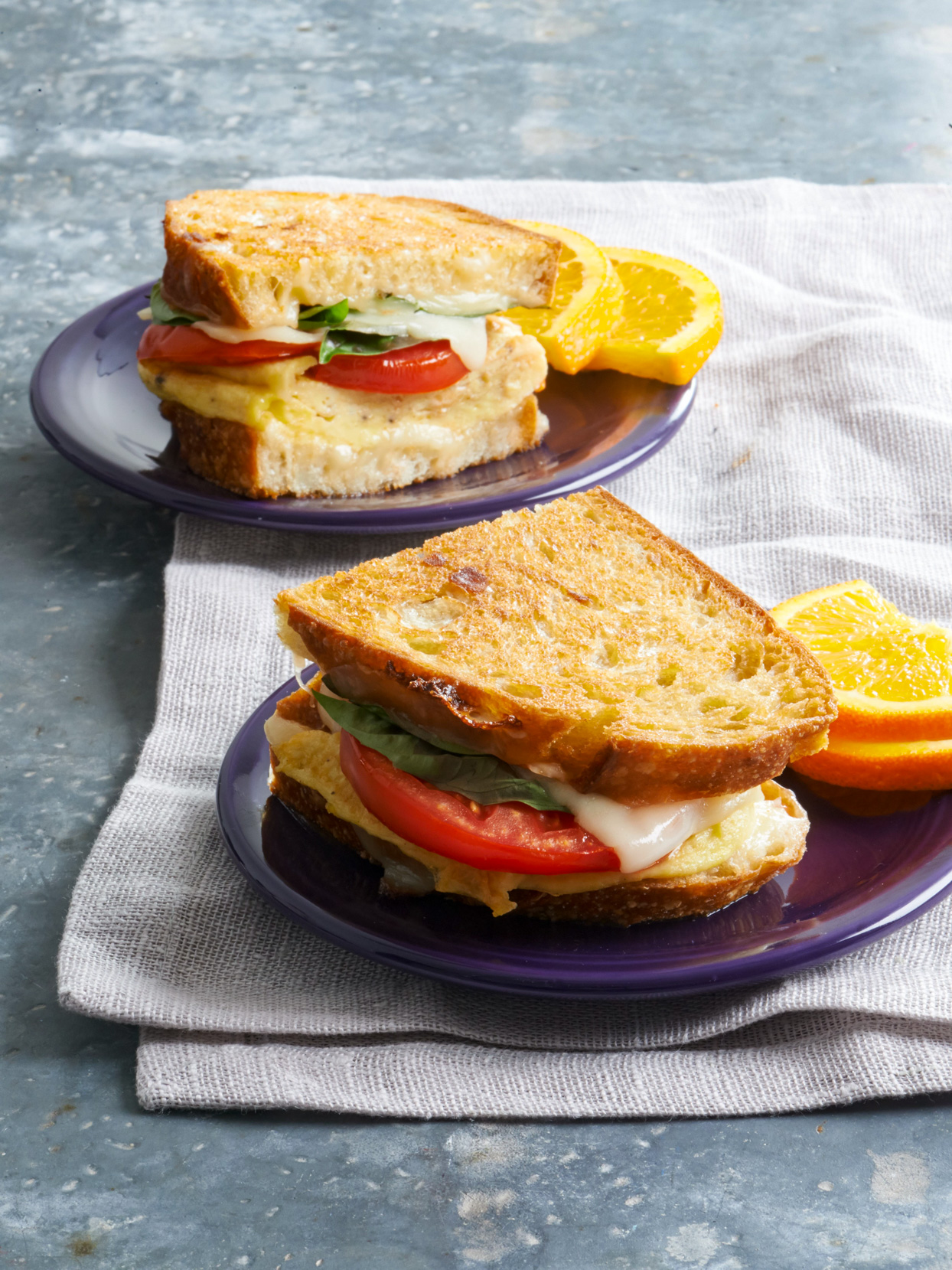 two Cheesy Egg Sandwiches on plates with orange slices