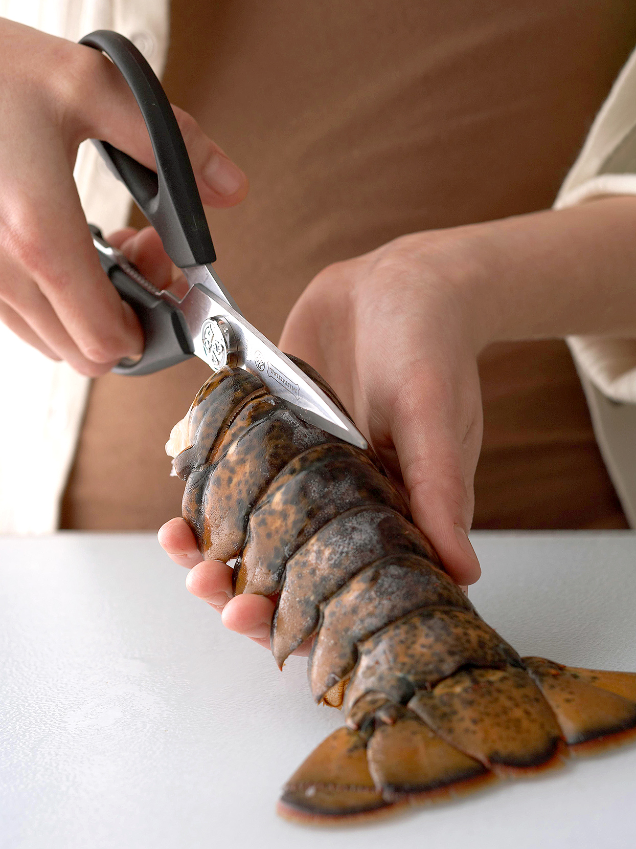 woman cutting top of lobster tail with scissors