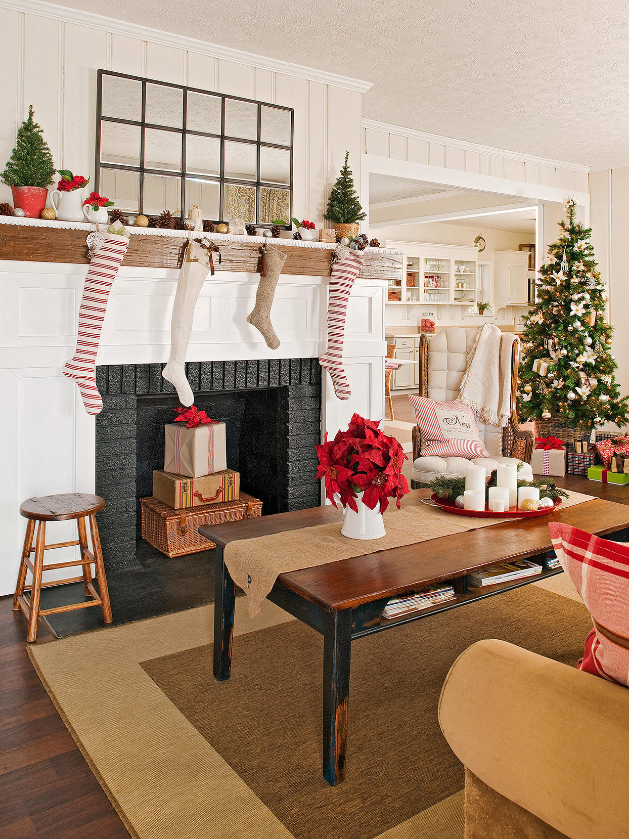 antique Christmas décor in cottage living room with stockings, small trees, and gifts