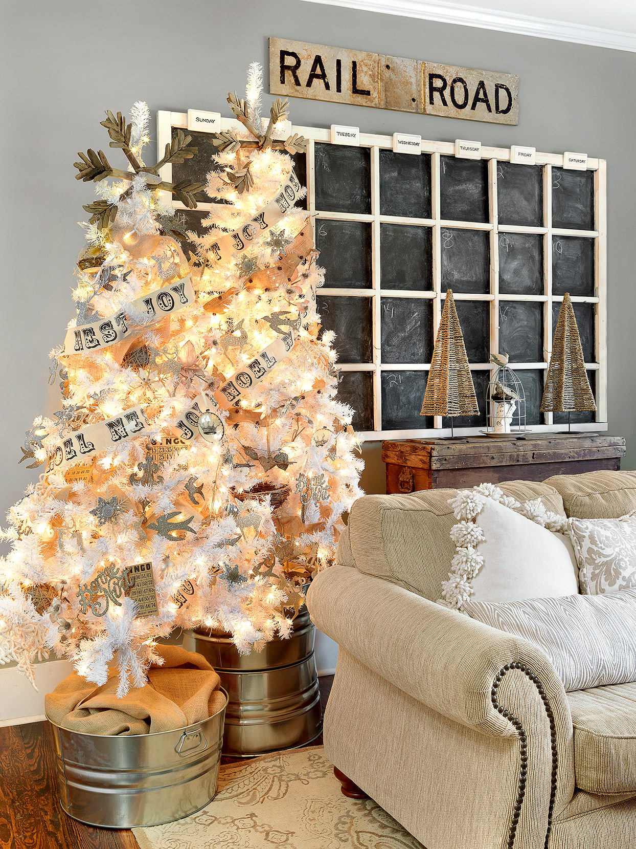 large chalkboard calendar in rustic living room near brightly lit white Christmas trees
