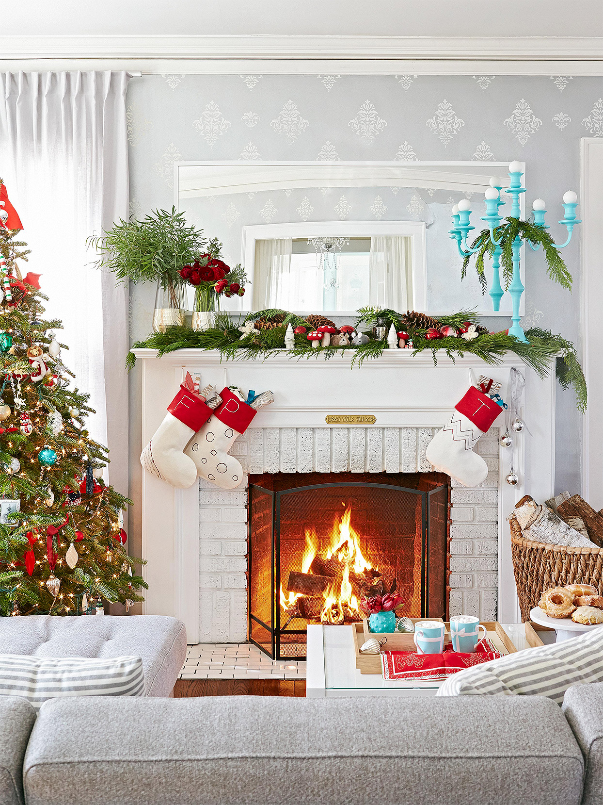 white fireplace mantel with Christmas swag, monogram stockings and turquoise candelabra