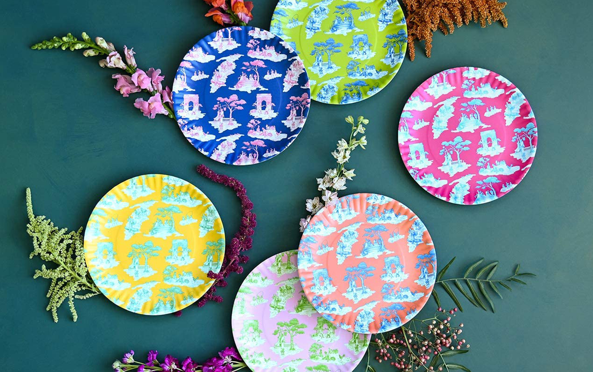 Colorful Toile patterned plates on a teal background