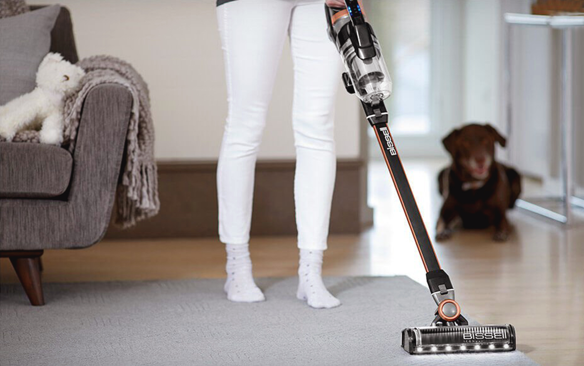 woman using a Bissell stick vacuum