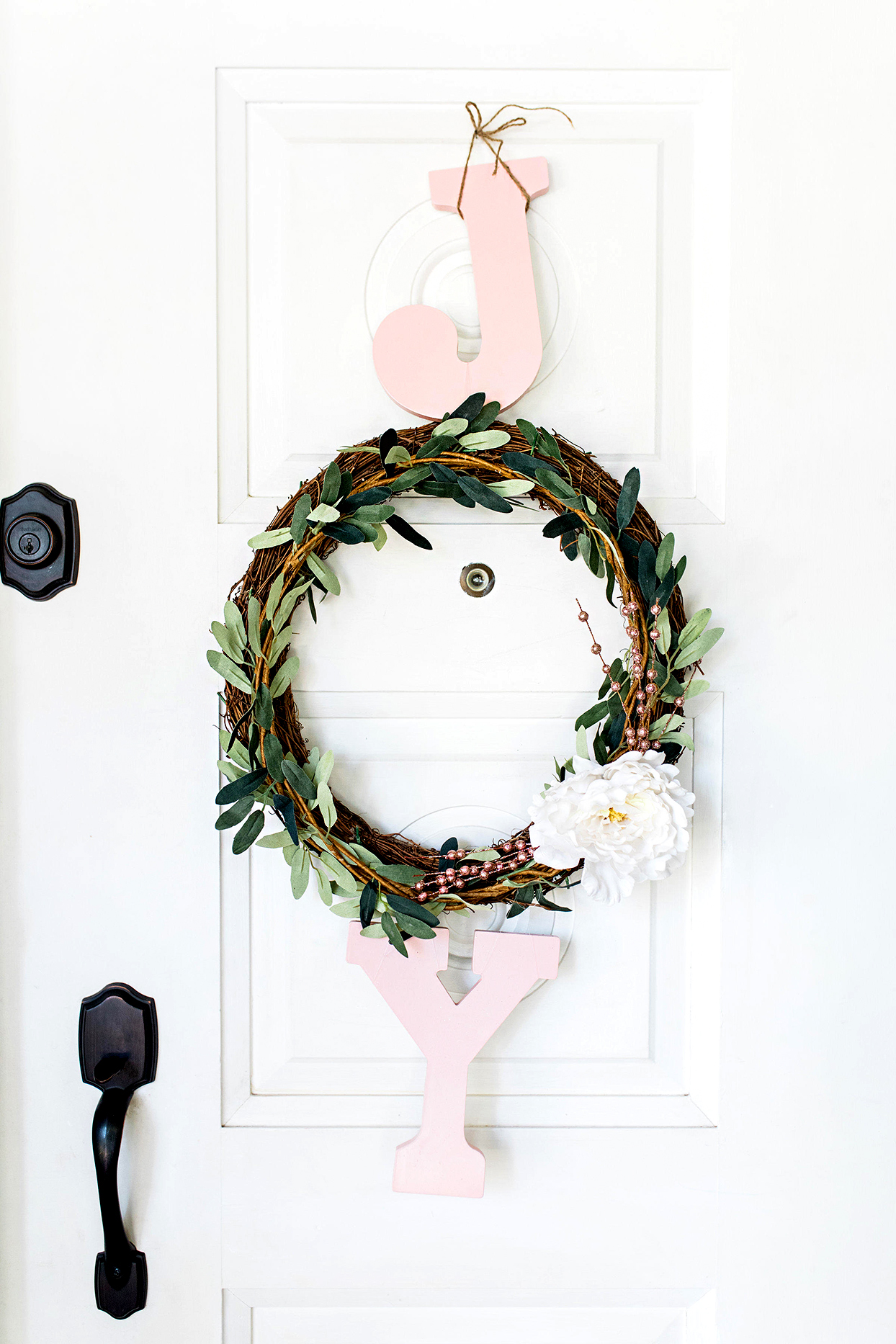 Close up of Christmas wreath with text hanging on door