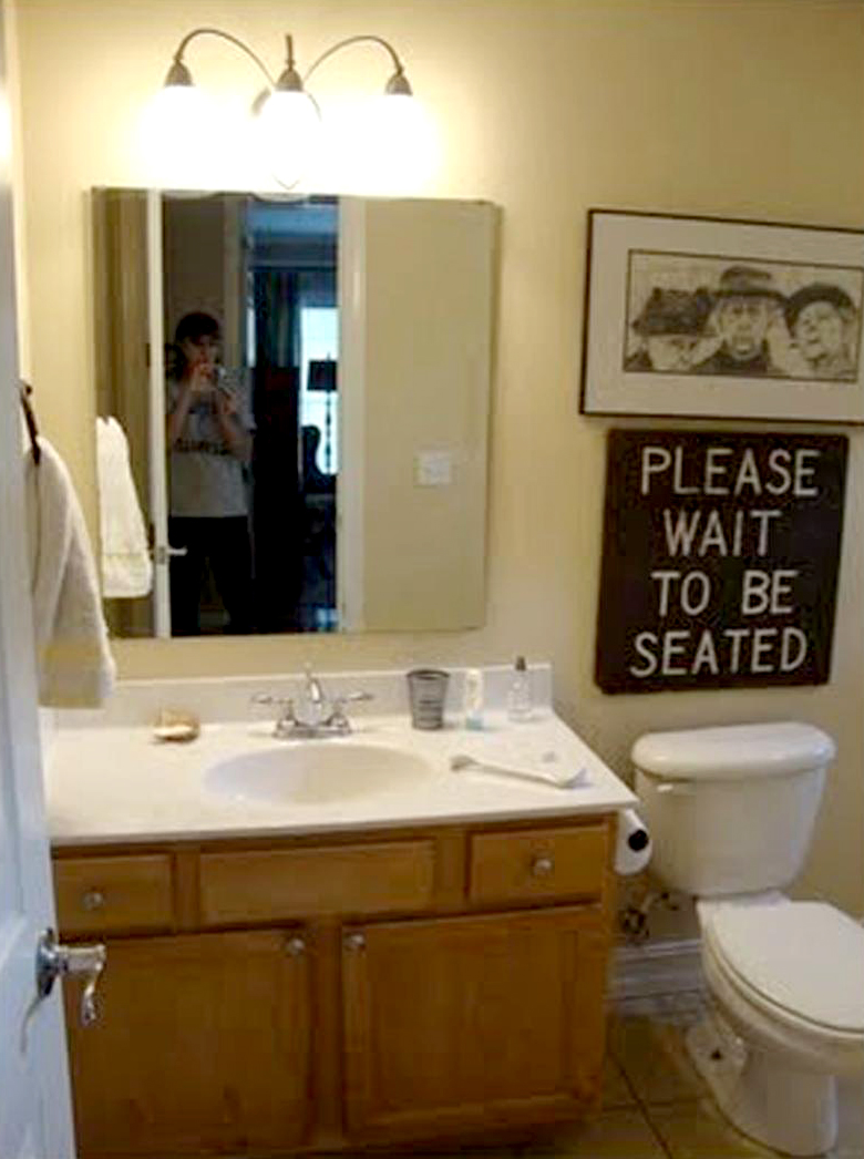 bathroom with yellow walls and sign