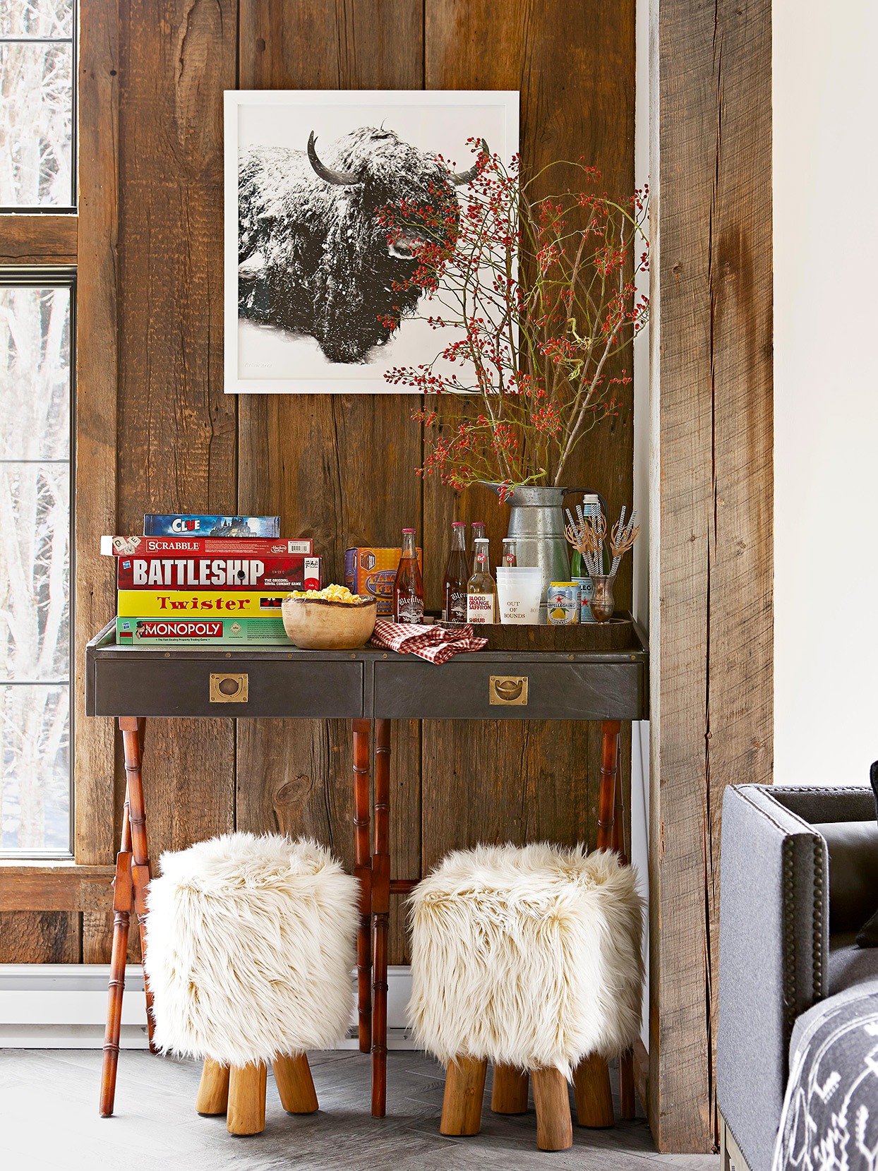 wood wall with games and drinks on traditional console table and sheepskin stools underneath