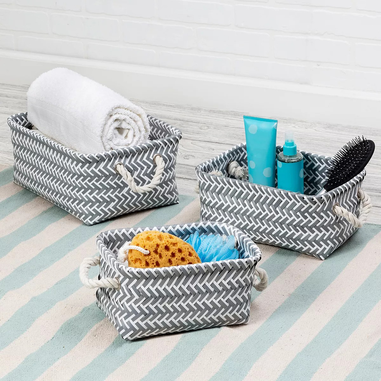 gray and white storage bins on striped rug