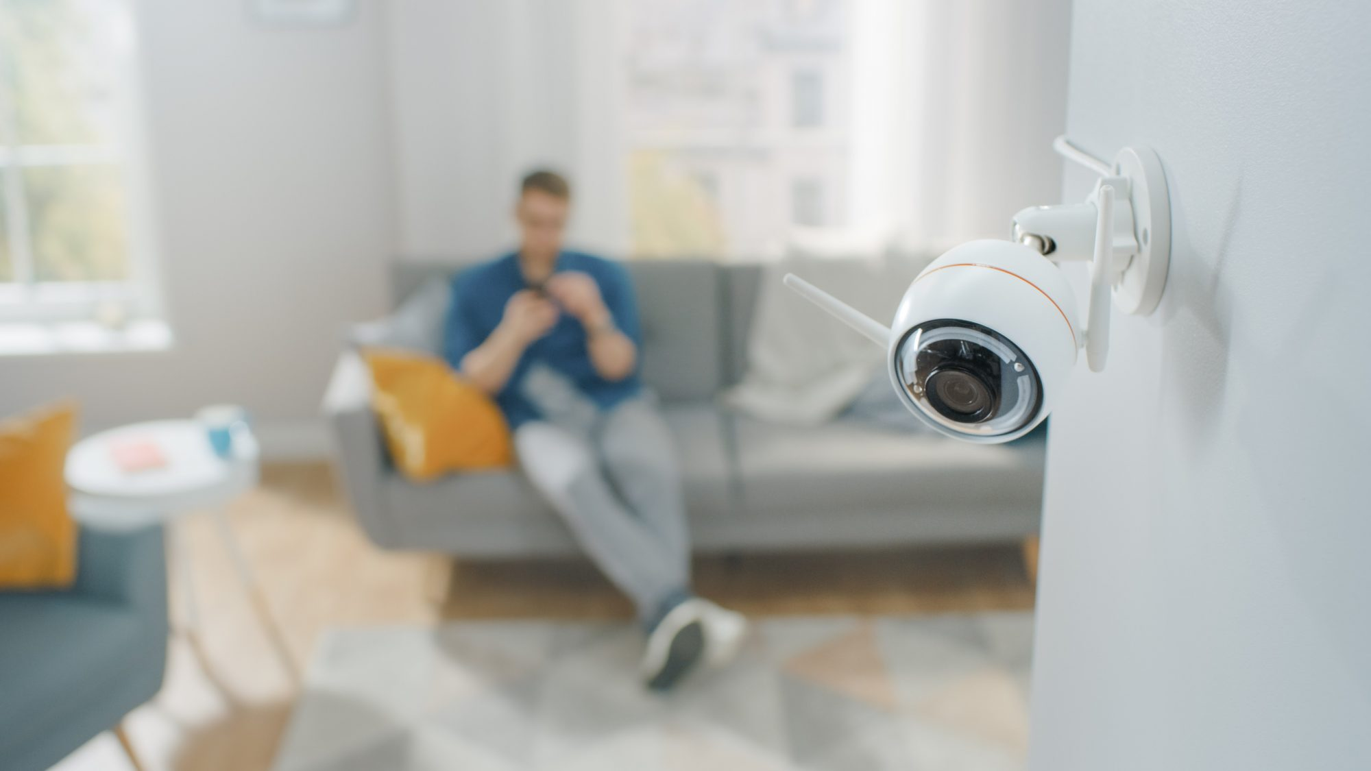 Close Up Object Shot of a Modern Wi-Fi Surveillance Camera with Two Antennas on a White Wall in a Cozy Apartment. Man is Sitting on a Sofa in the Background.