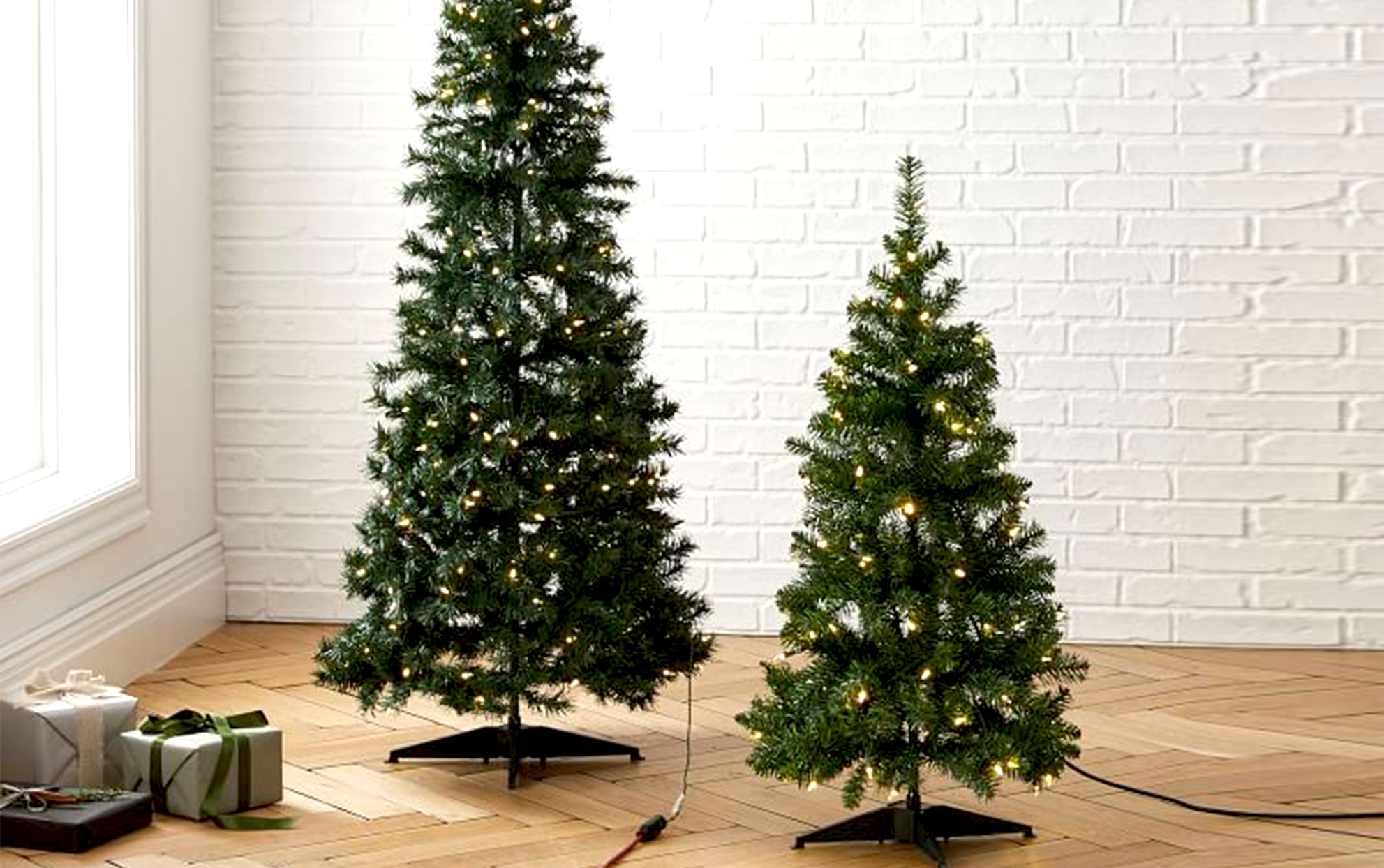 Pop-up Christmas trees with a white brick wall behind