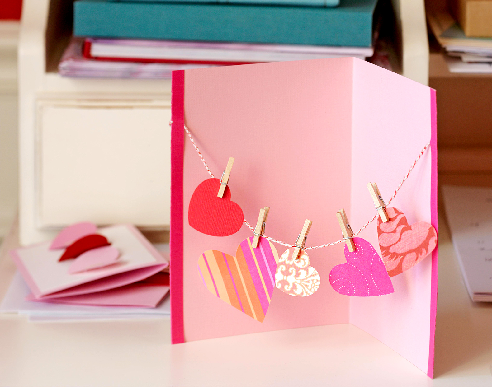 valentines card with 5 hearts clipped to string