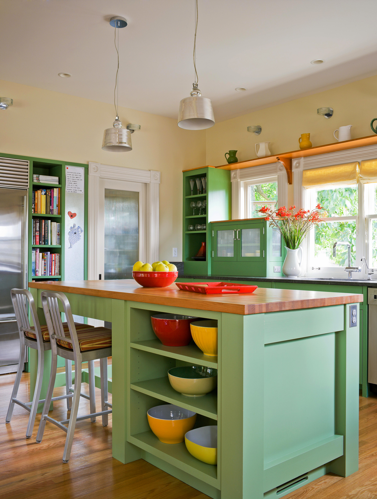 green kitchen cabinets with silver pendant lights