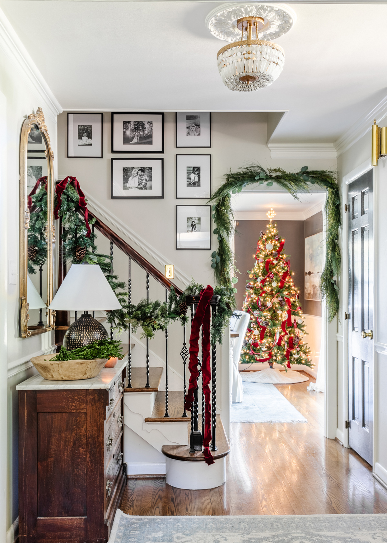 entryway with evergreen garlands and christmas tree