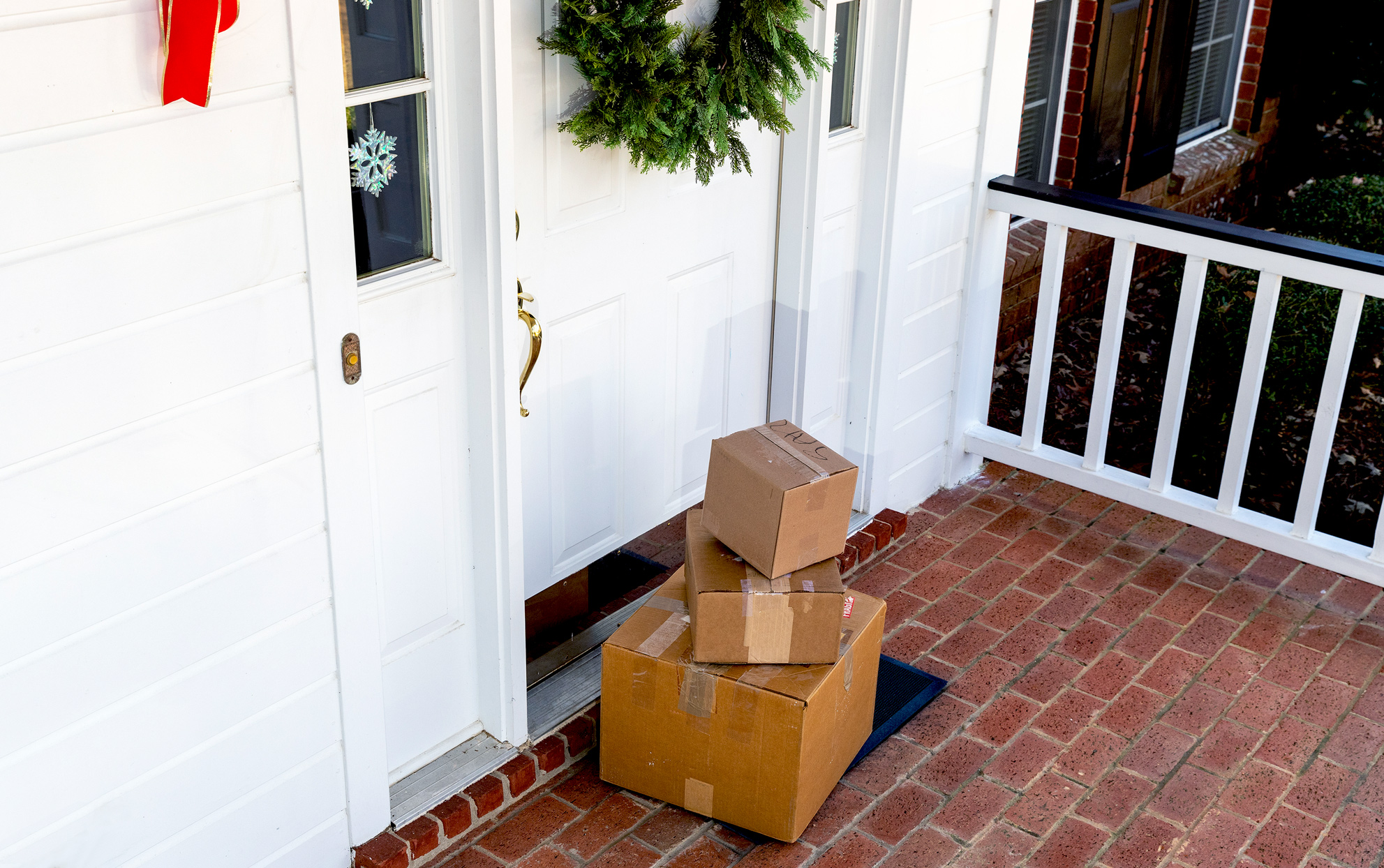 A stack of shipping boxes on a front porch