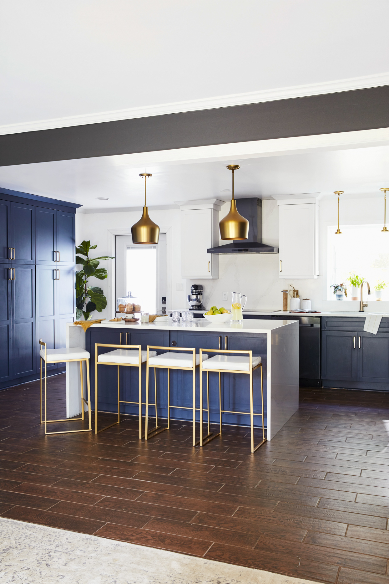 modern kitchen with dark wood floors and gold hanging lights