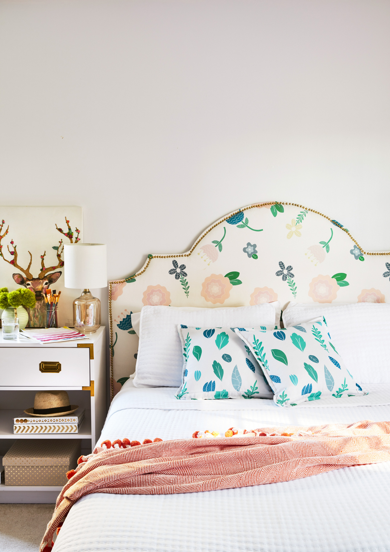 pastel bedroom with patterned headboard and pillows