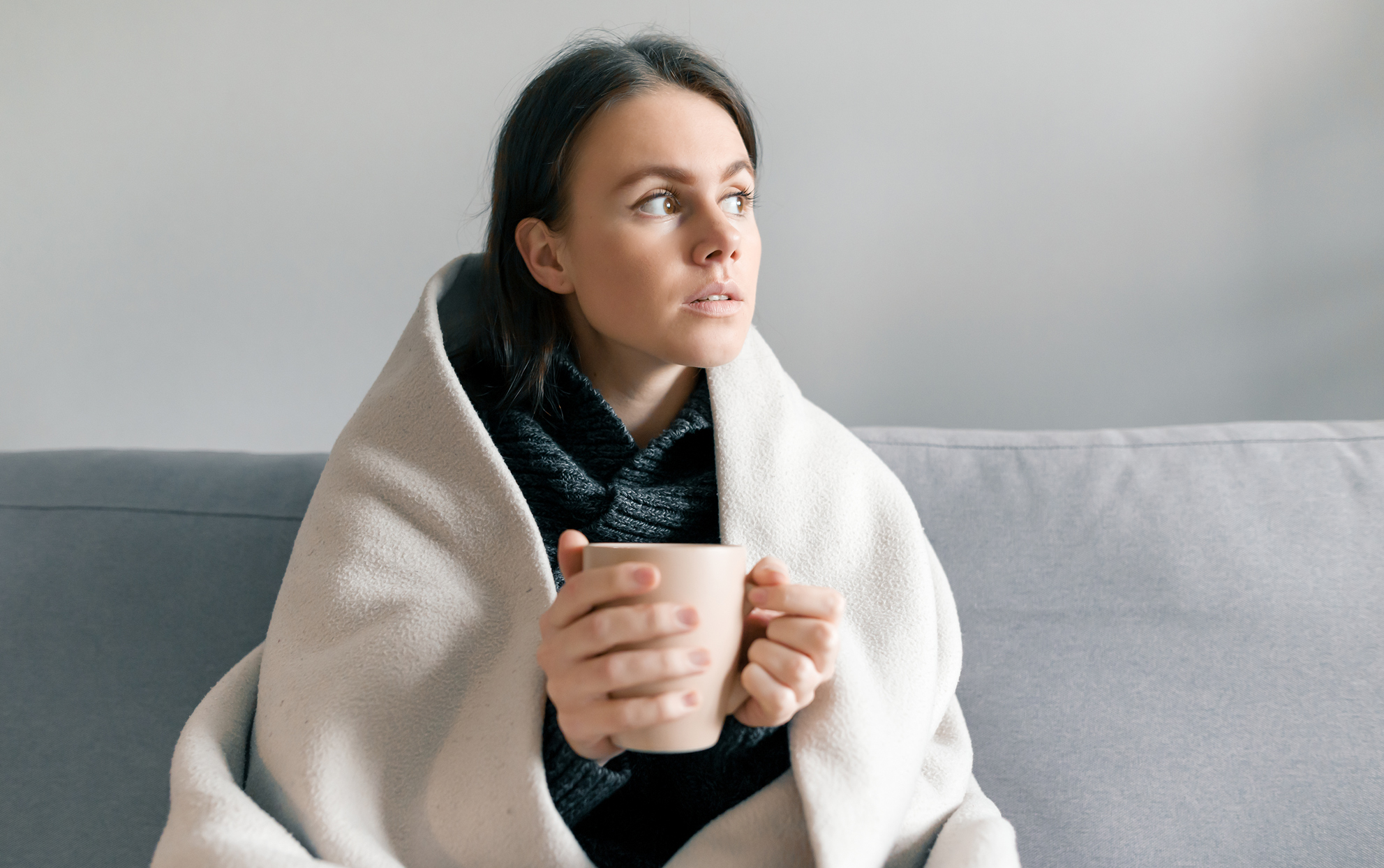 Woman on a sofa under a blanket drinking from a mug