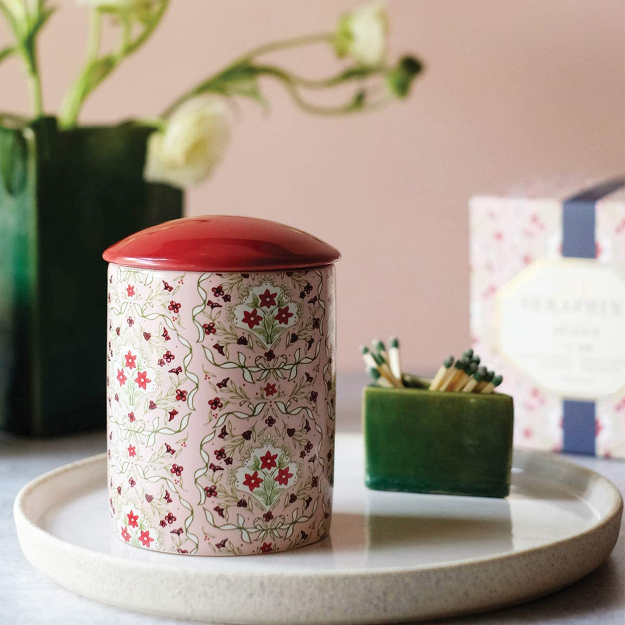 pink floral jar candle with red lid on tray