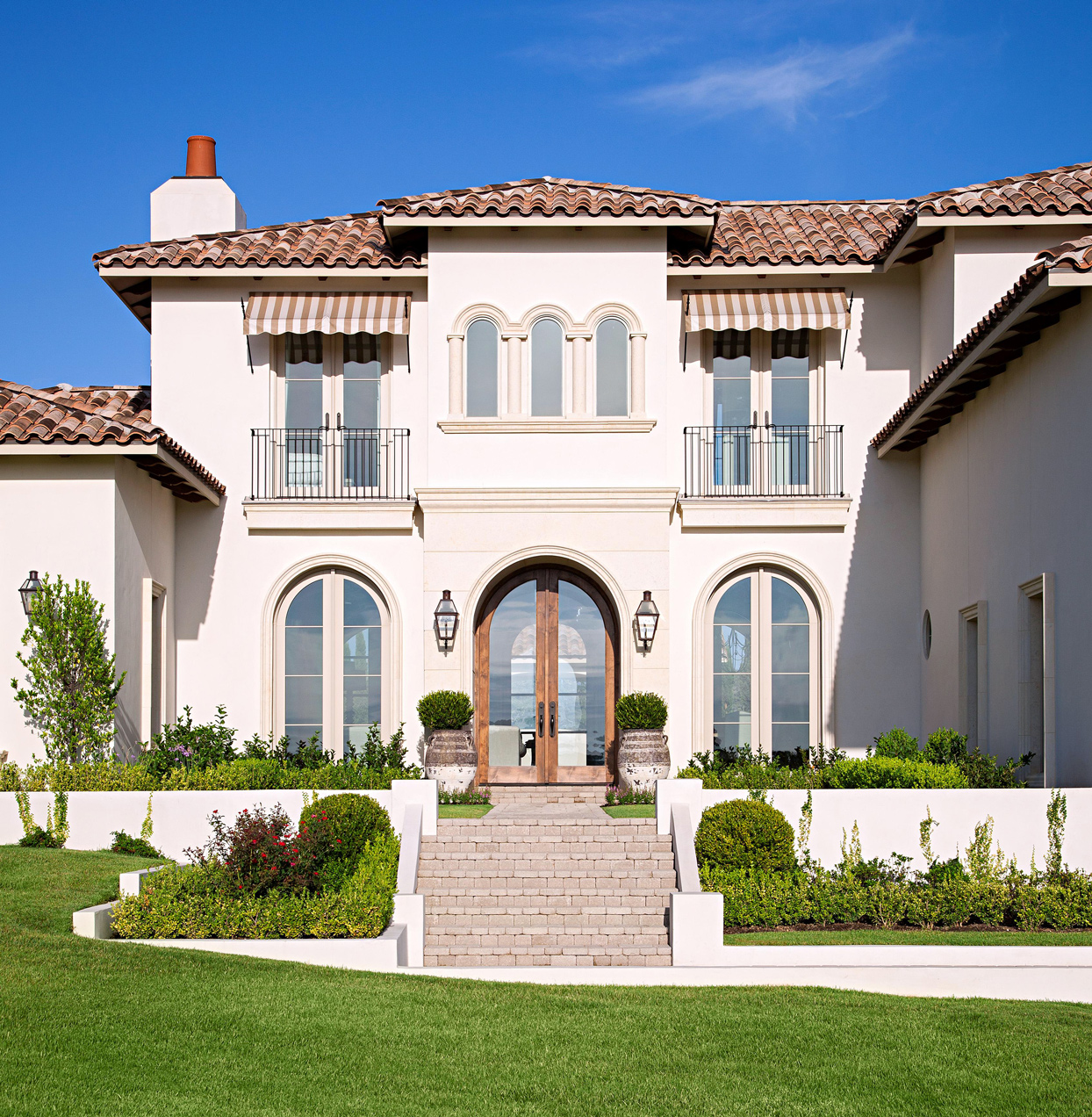 stucco home with clay roof tiles and french door