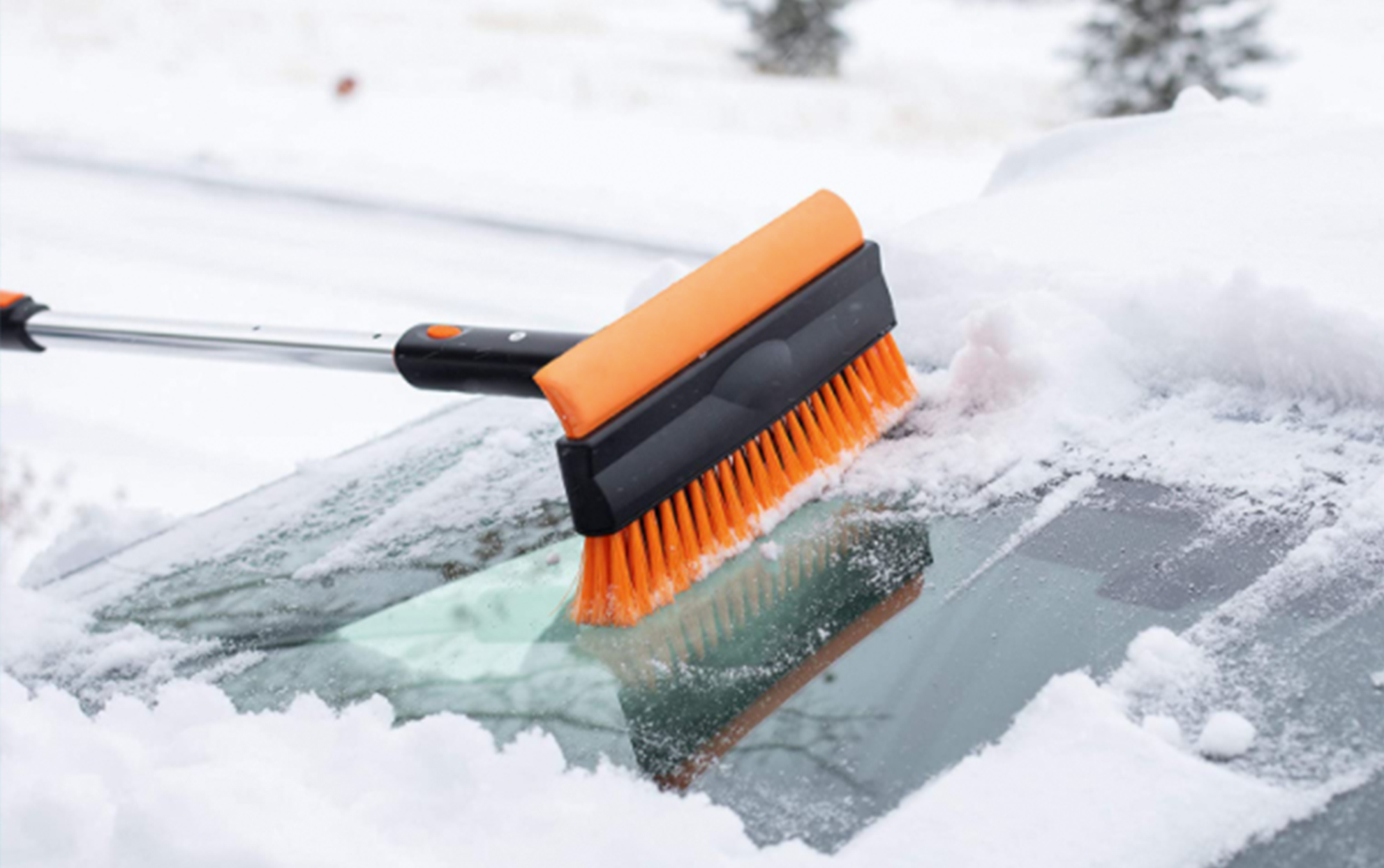 Extendable Snow Brush & Ice Scraper being used on a windshield