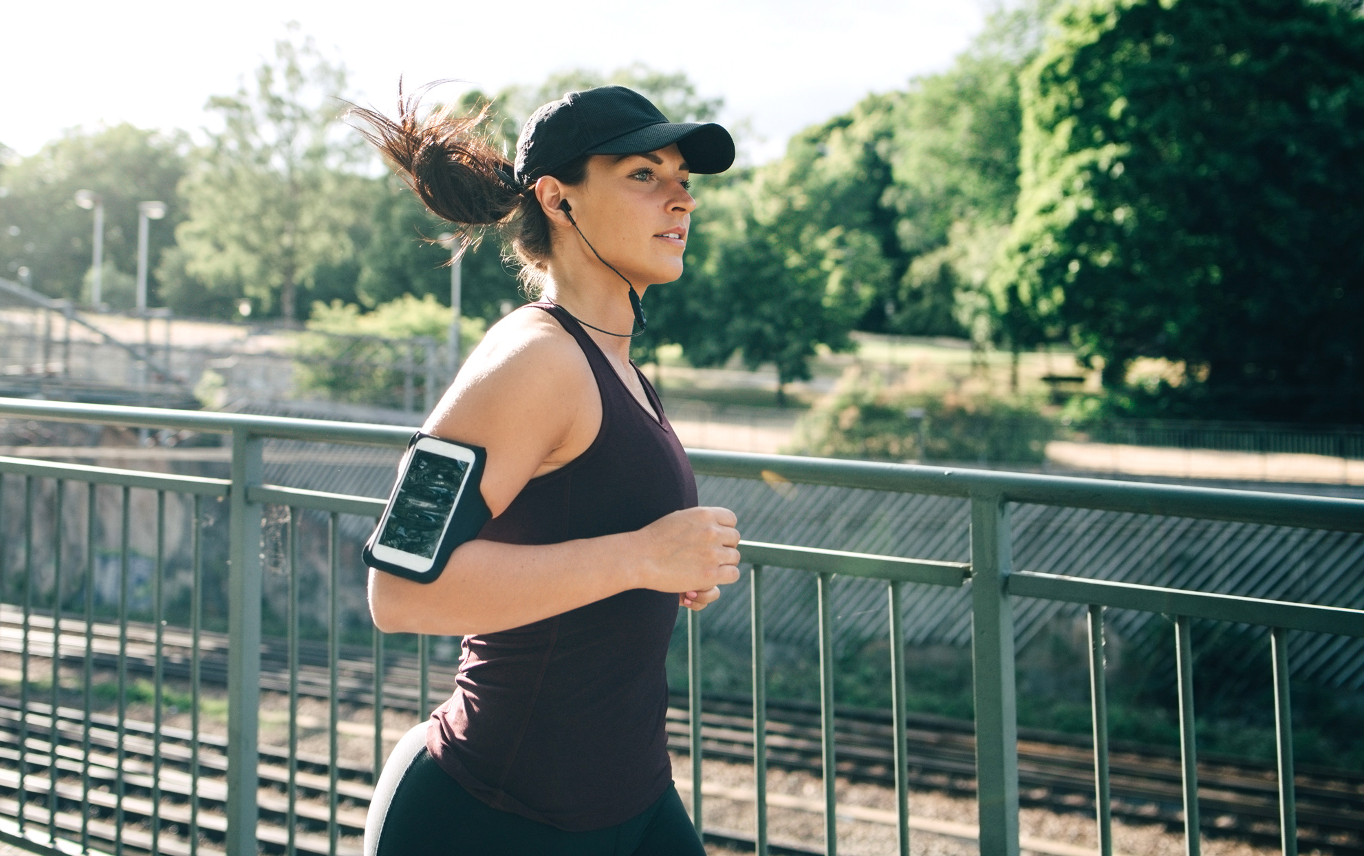 woman running outside with earbuds listening on her cell phone