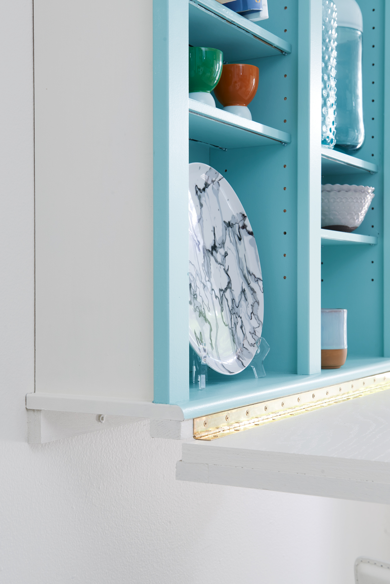 Open blue cabinets with dishes