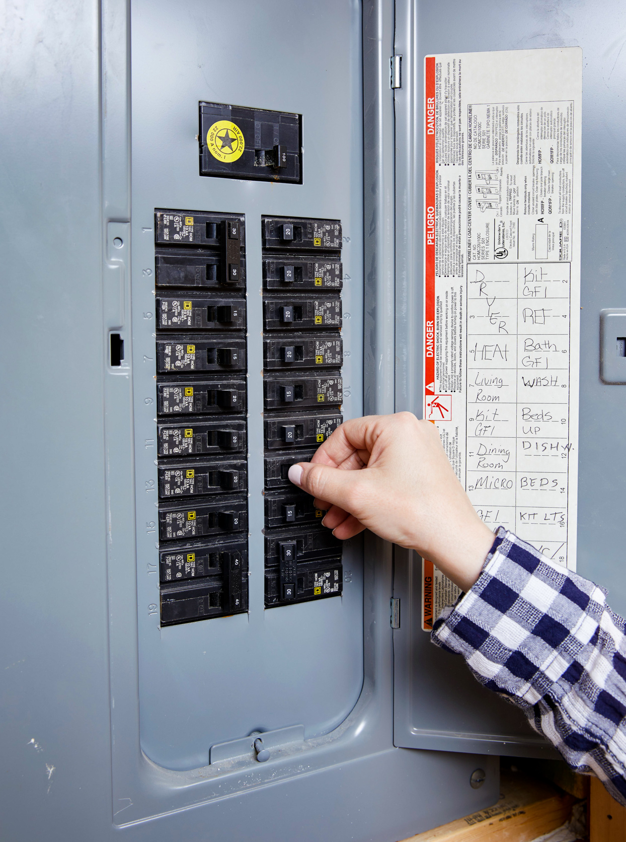 person flipping switch in circuit box