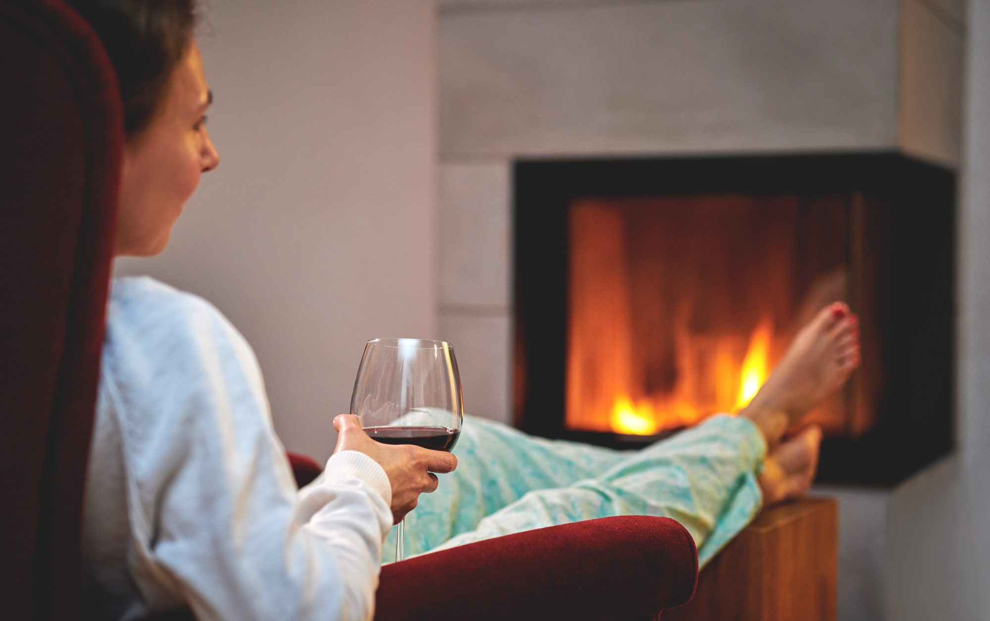 woman sitting by the fire with a glass of wine