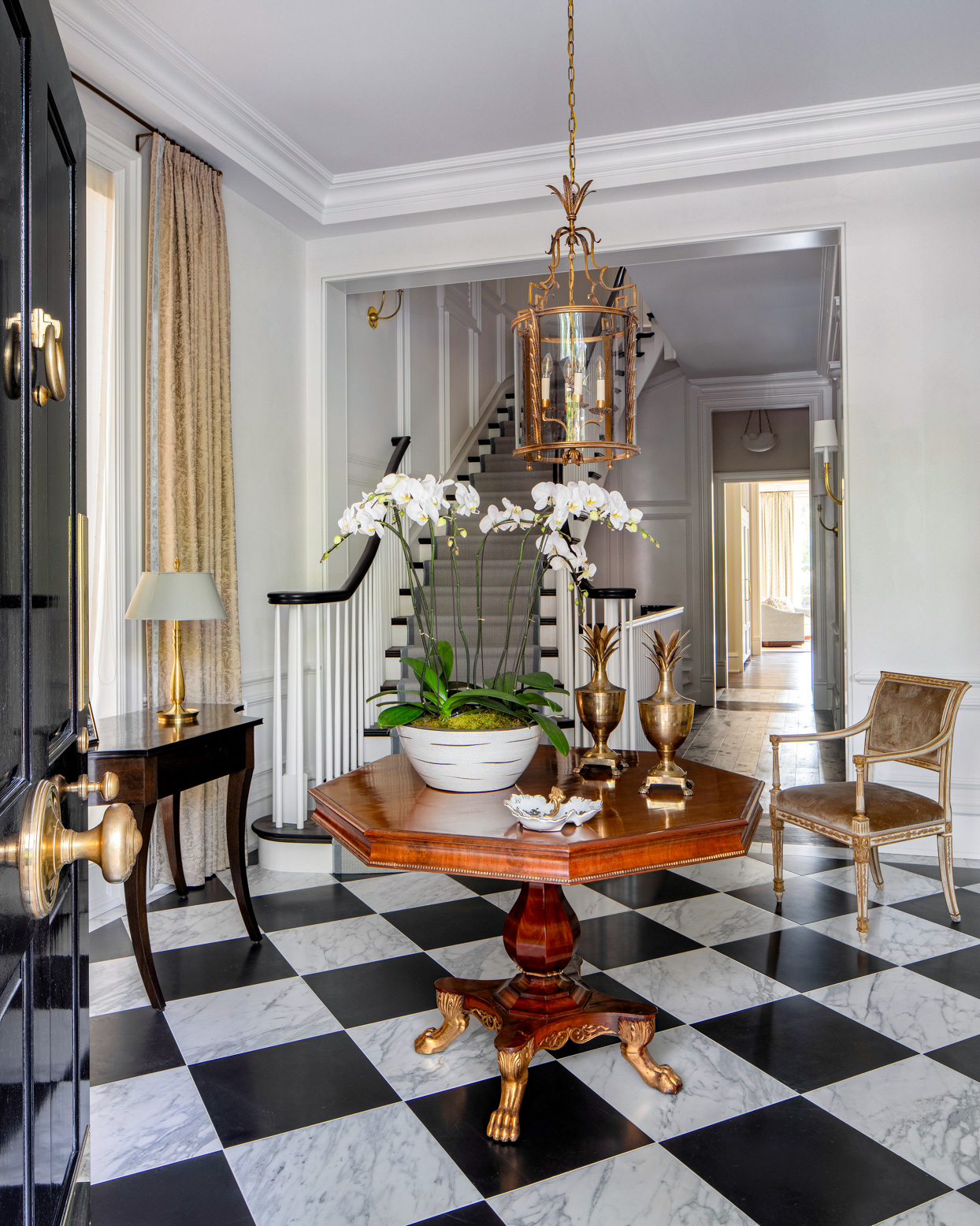 entry area with gold accents and black and white tiled floor