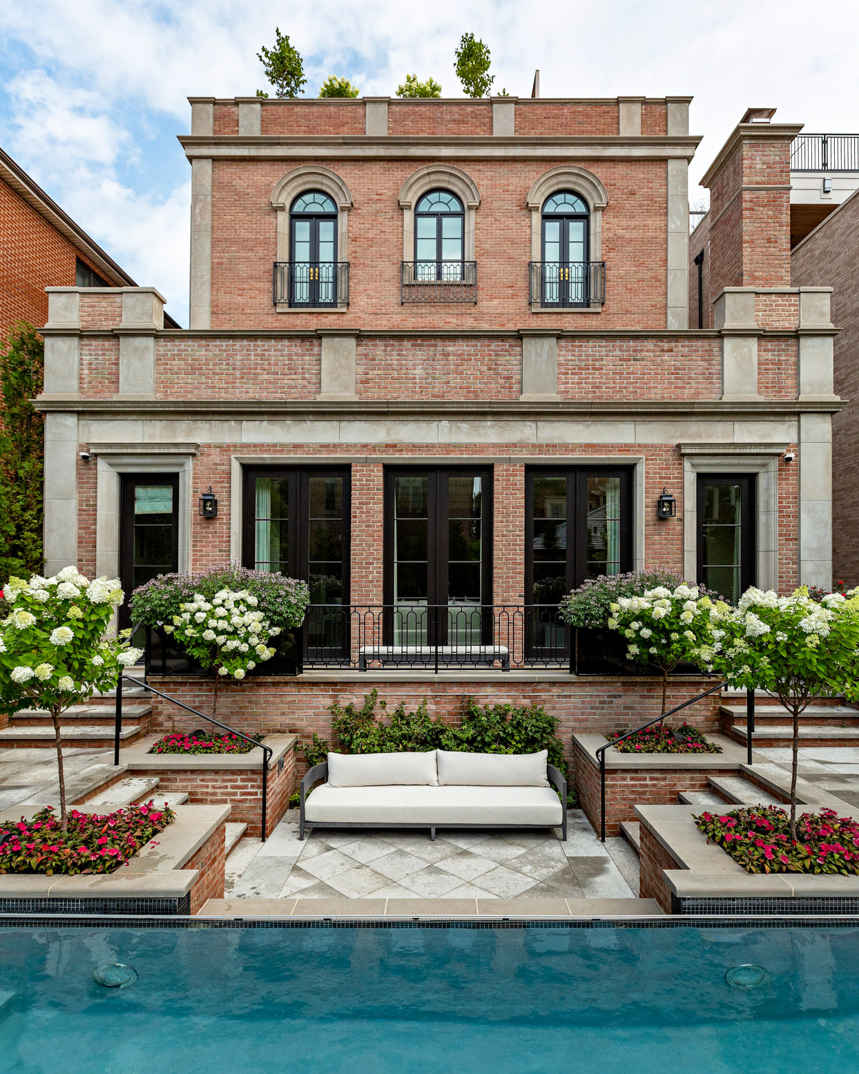 exterior shot of brick home with swimming pool