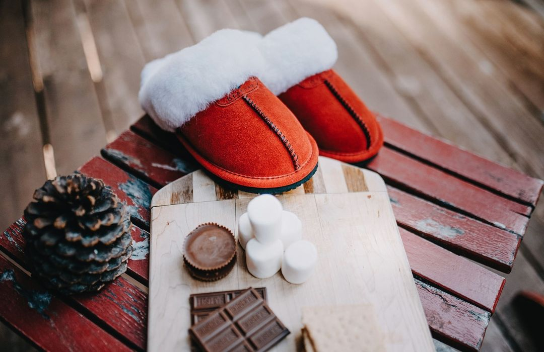 red Bearpaw Loki slippers near pine cone cutting board and smore ingredients