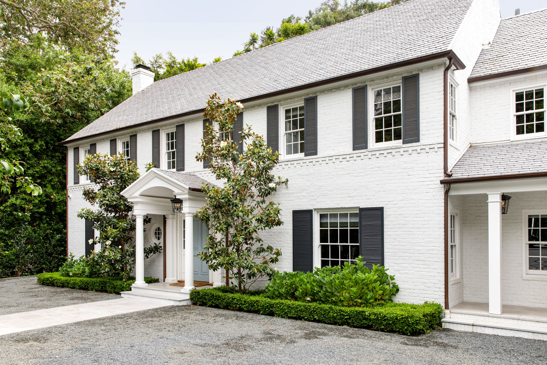 white brick home exterior with stately greenery