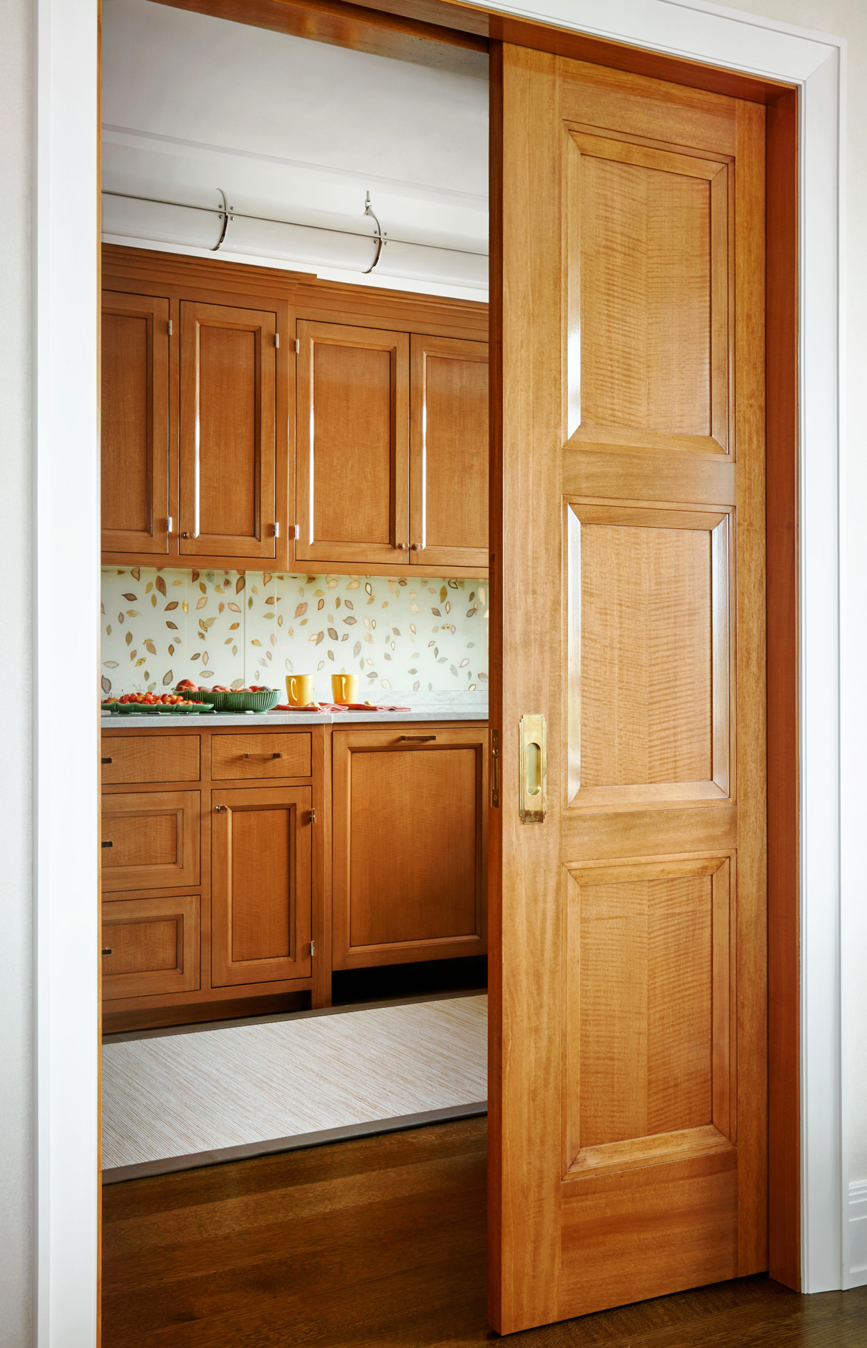Pocket door opening to small kitchen with wooden cabinets