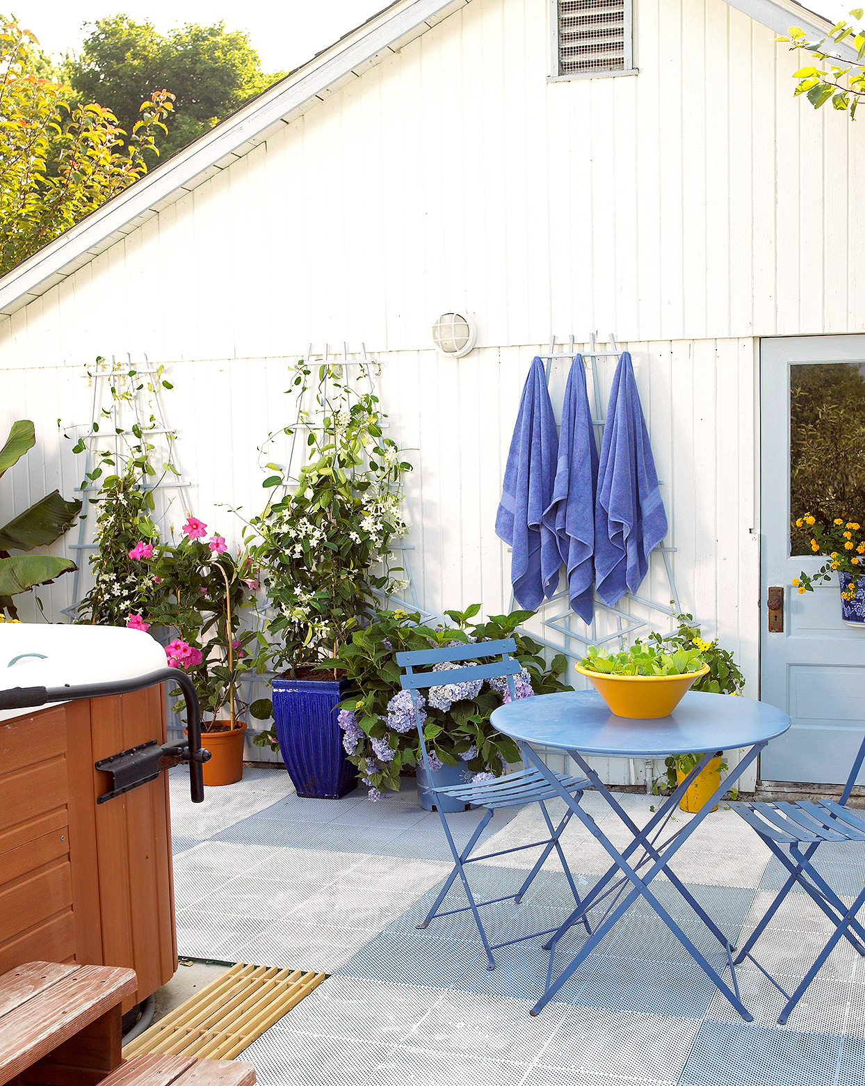 trio of trellises with vines and blue towels on patio