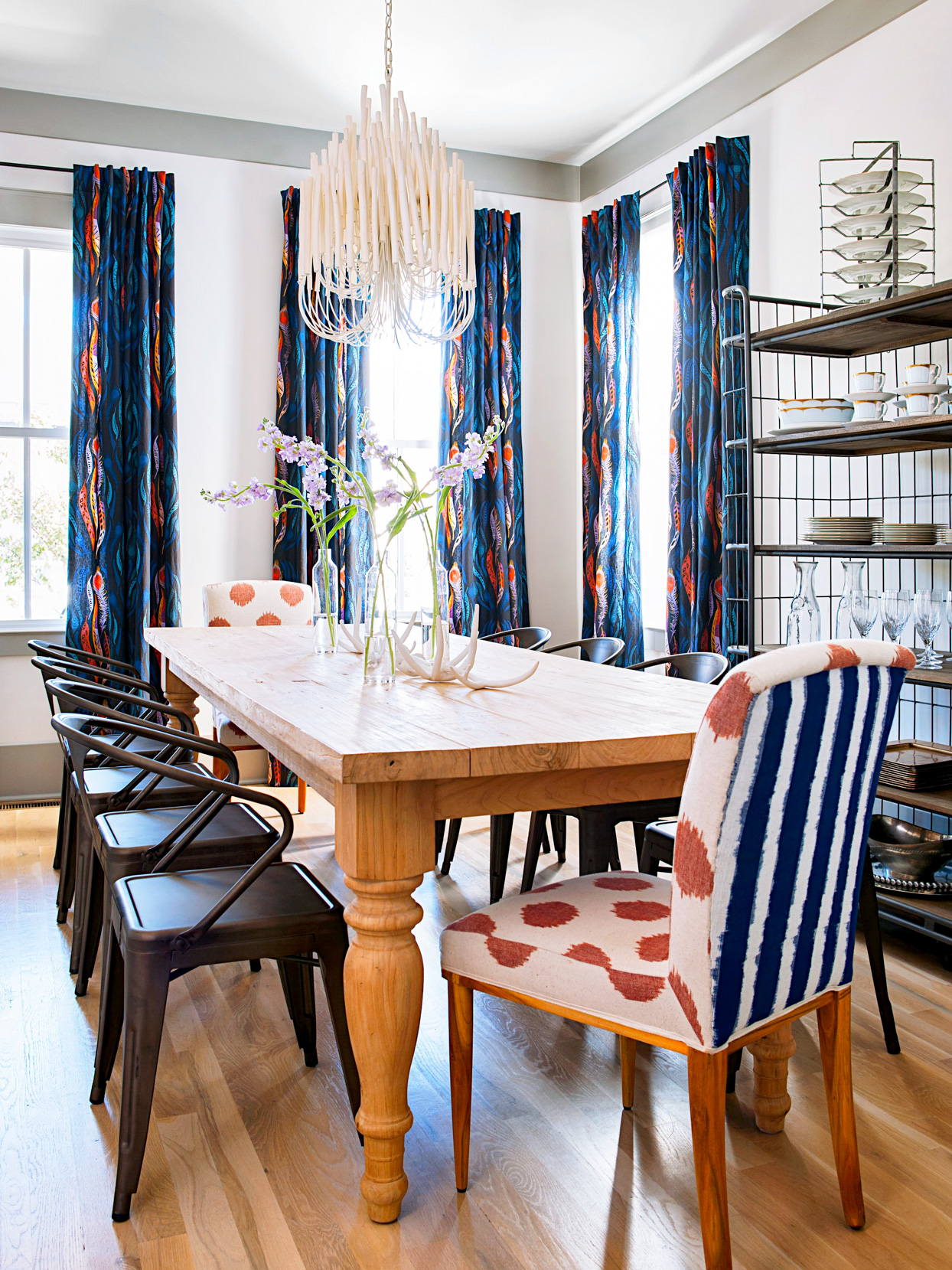 dining room with patterned blue and orange chairs and curtains