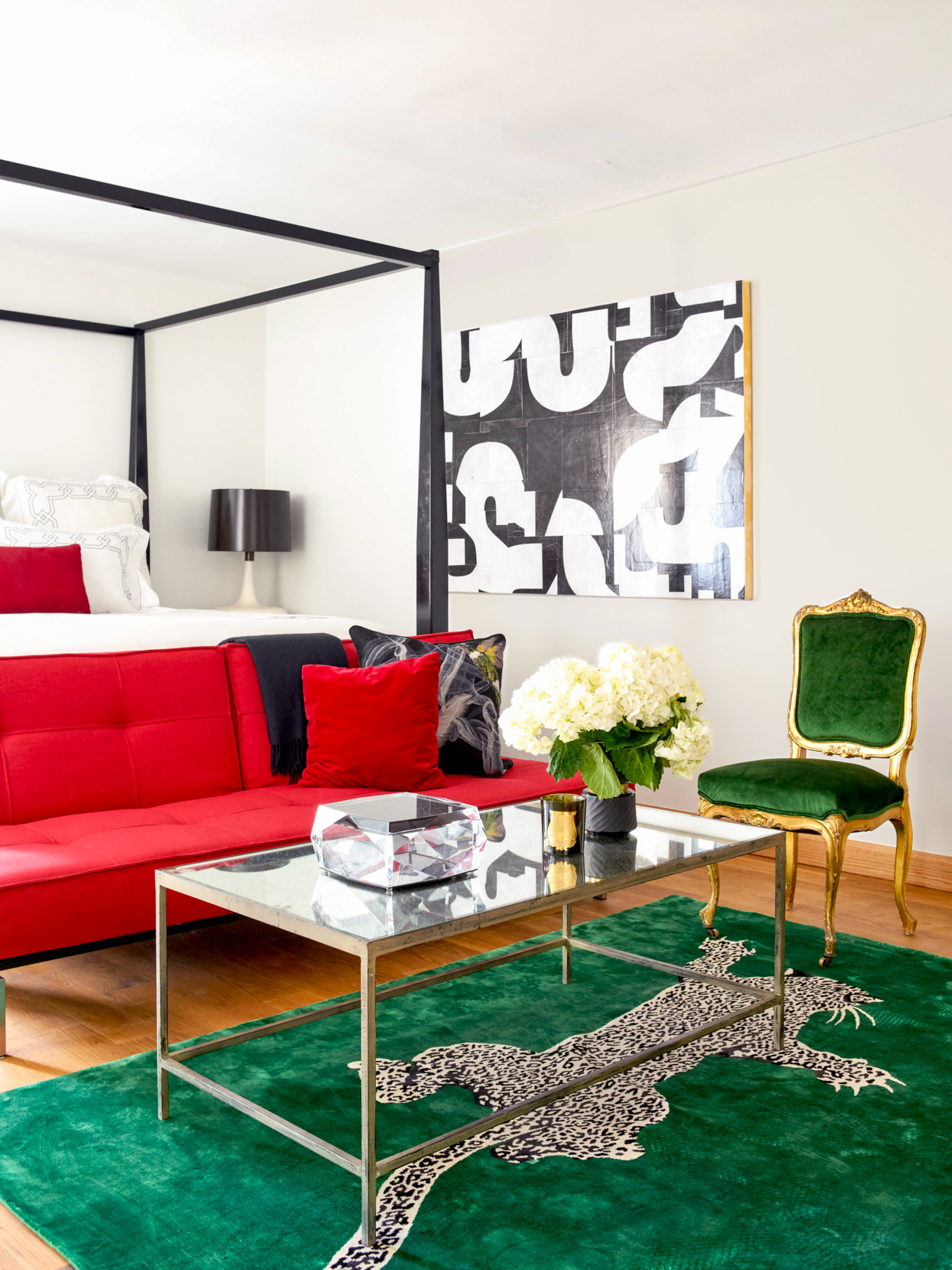 modern living room with red couch and green rug and chair