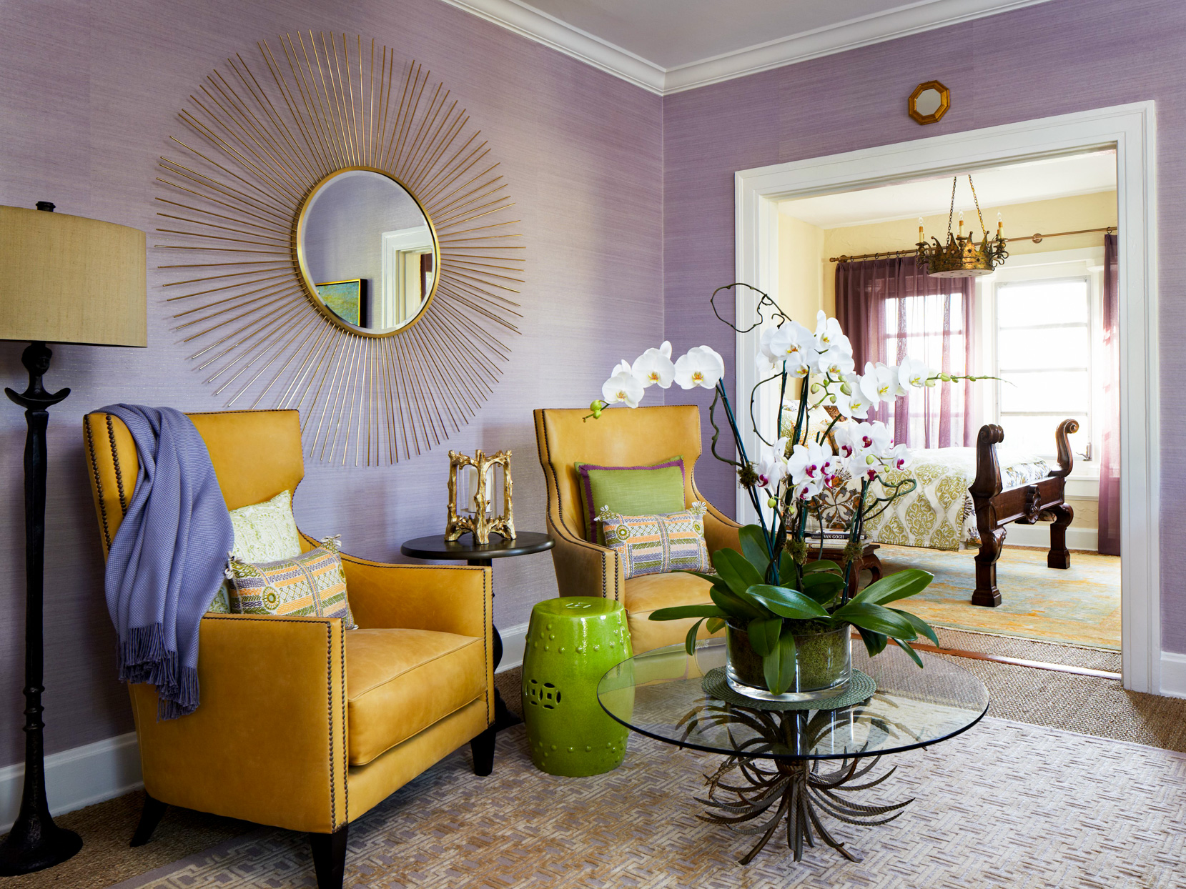 purple and yellow sitting room with glass table and round mirror