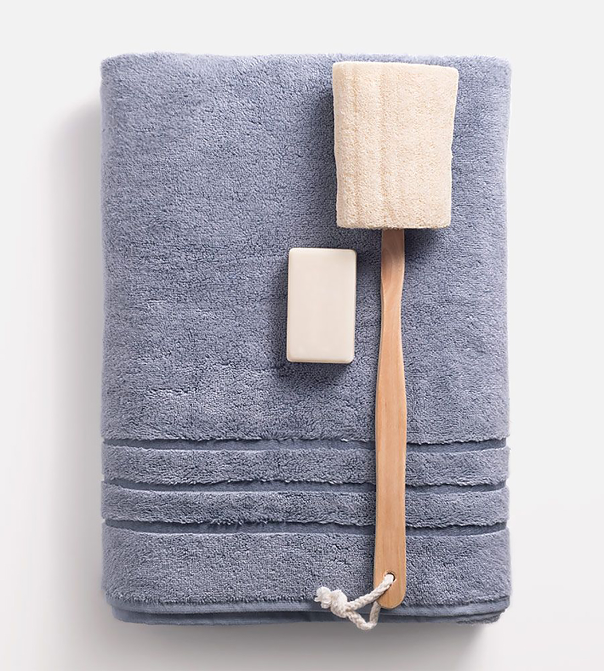 folded purple bath towel with soap and scrubbing brush on top