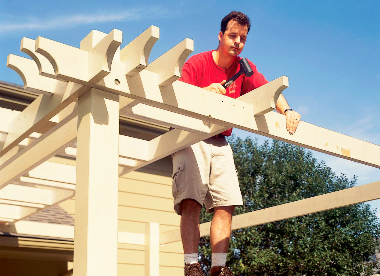 person using hammer to build pergola