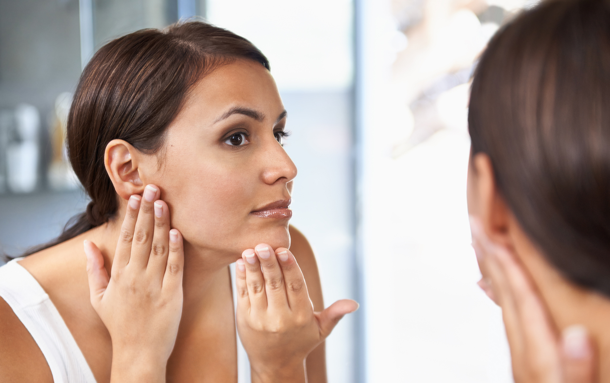 Ethnic woman looking at herself in the mirror