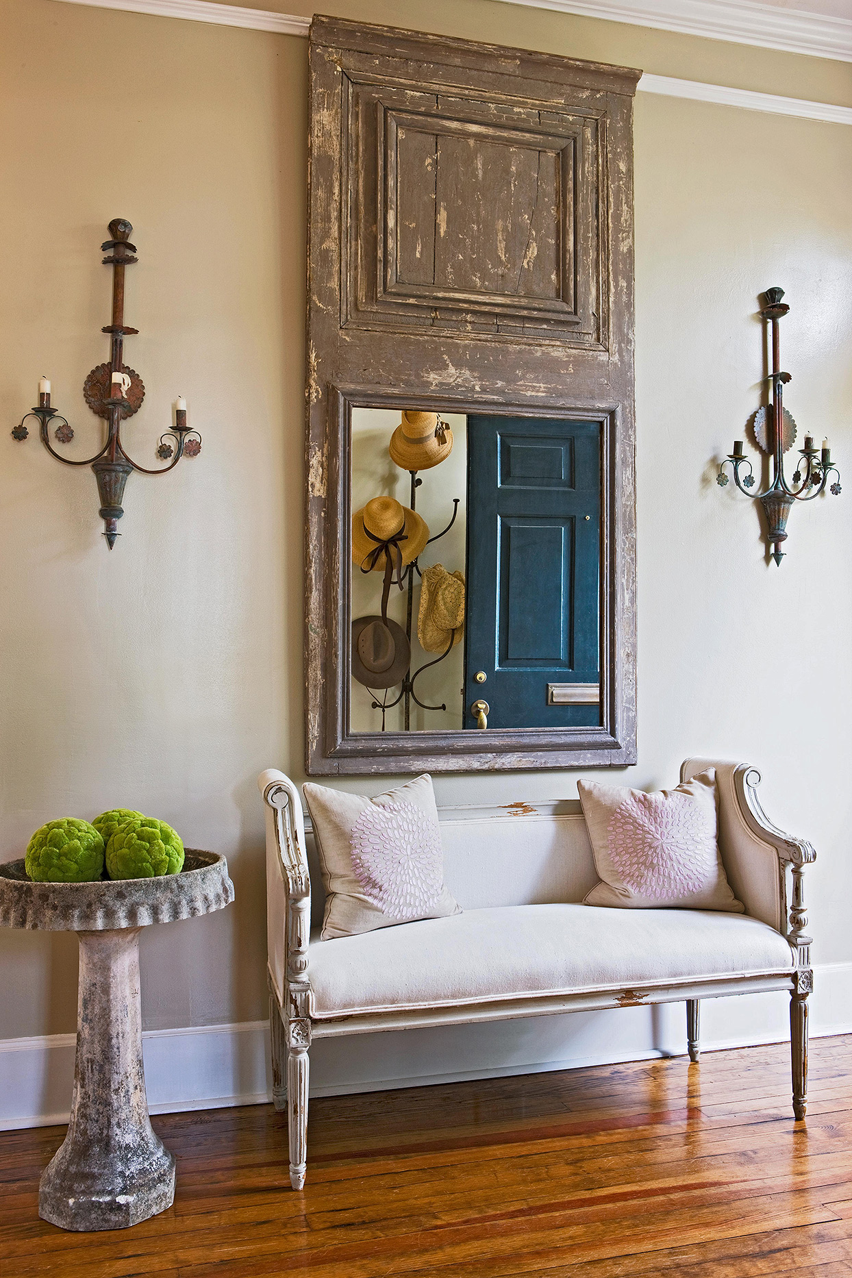 country french entryway oversize mirror ornate sconces upholstered bench