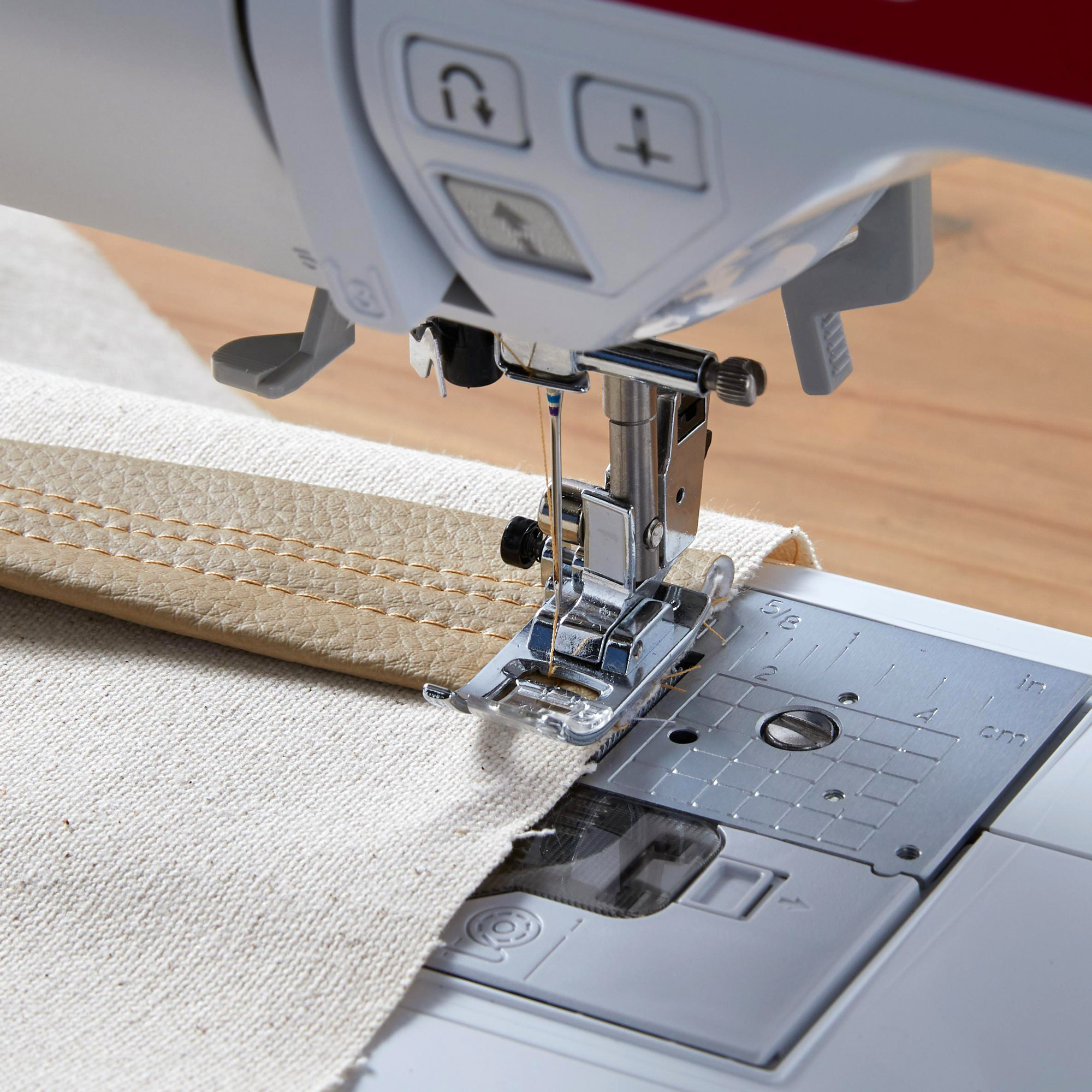 sewing machine stitching leather strap to canvas