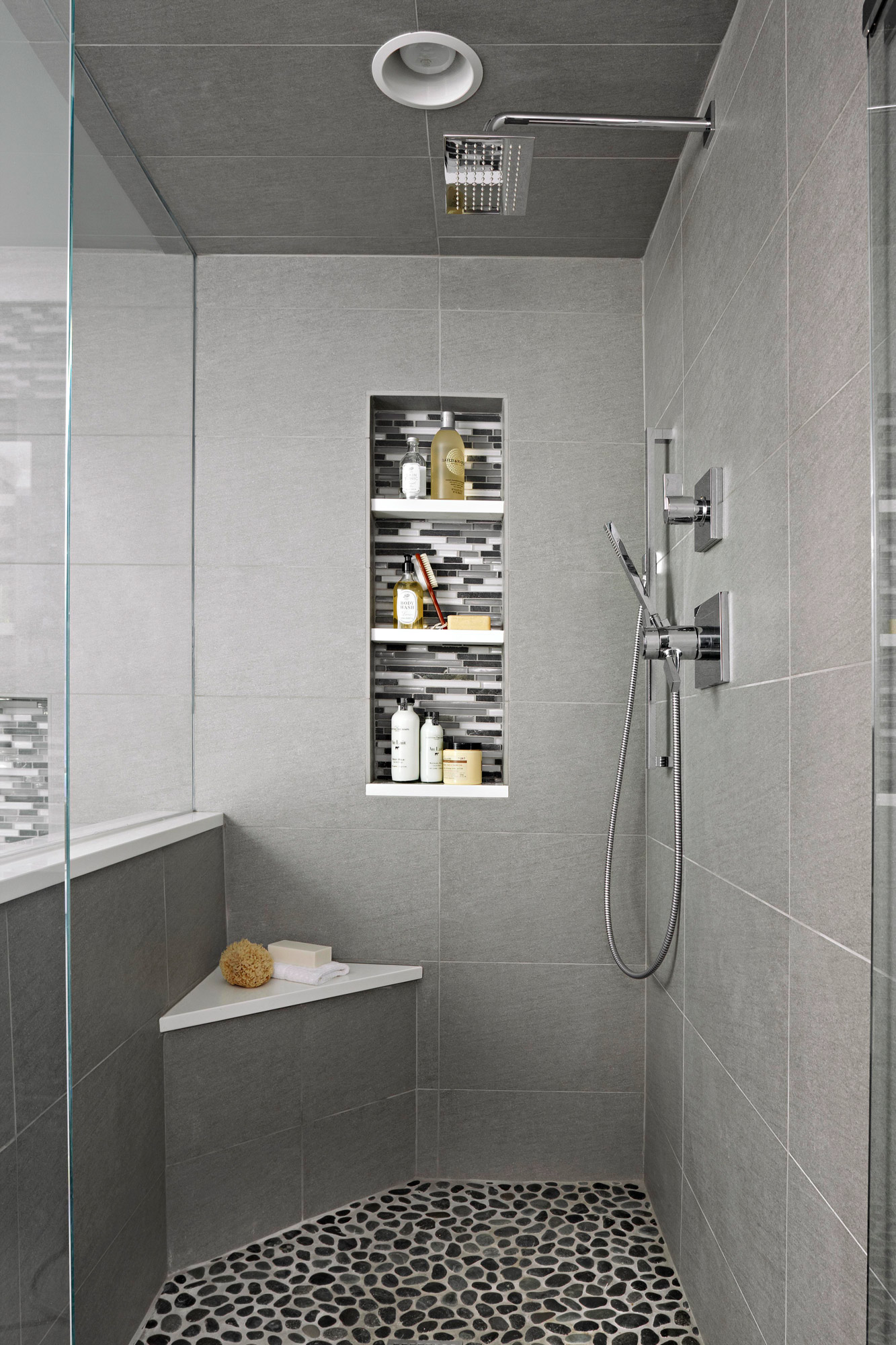 shower with gray tile and built-in shelves