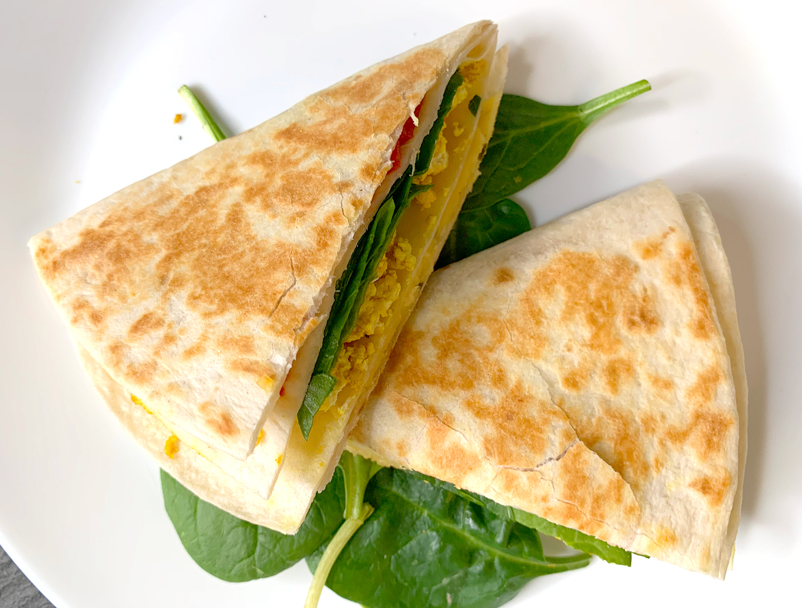 tortilla wrap on white plate with spinach