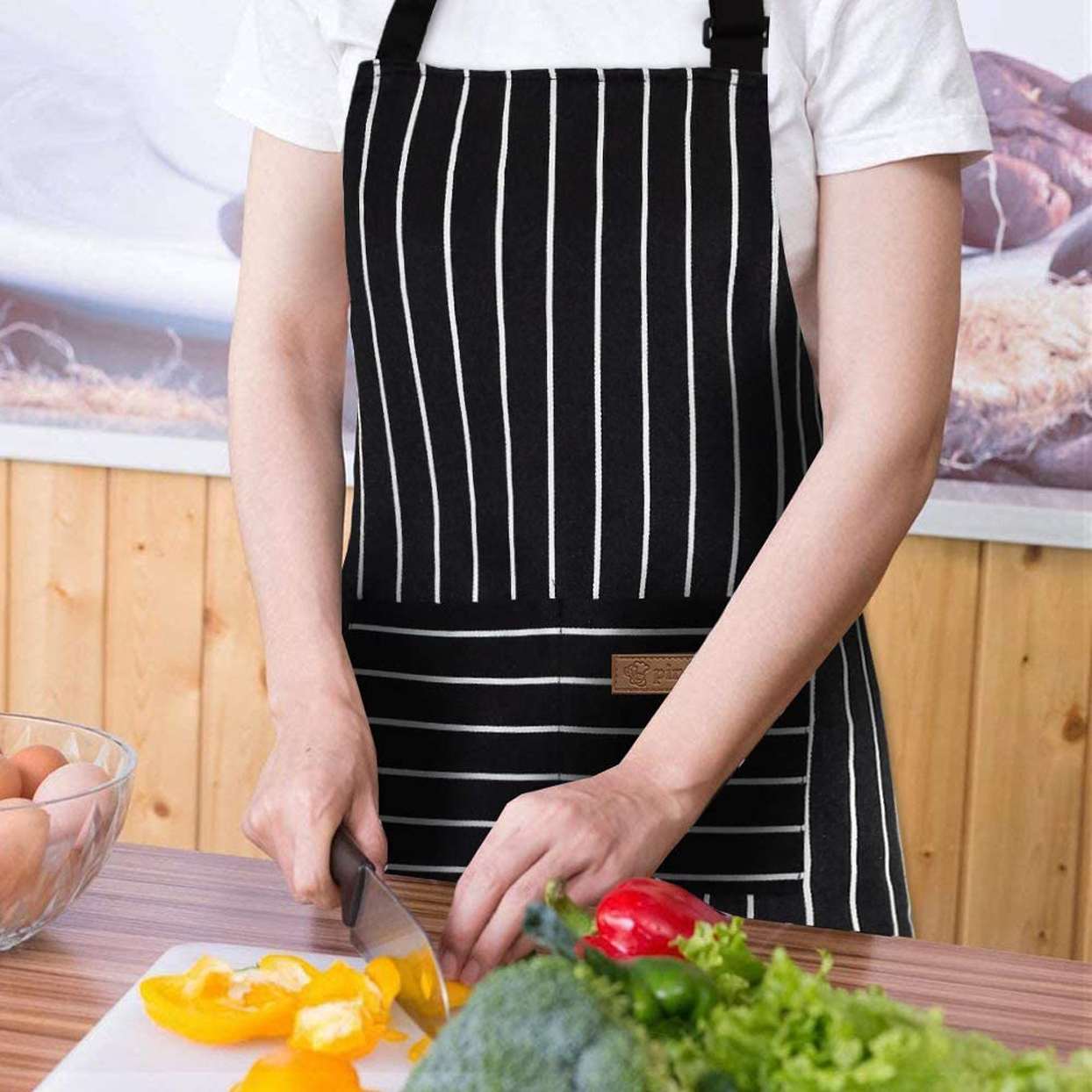 Person wearing a striped apron while cutting vegetables