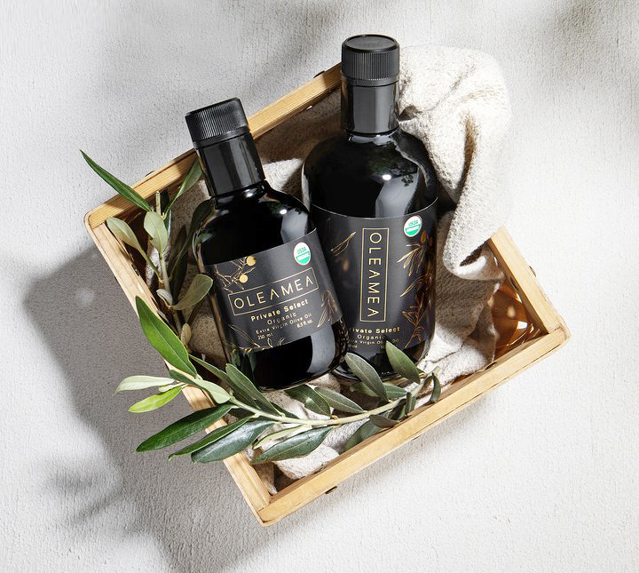 Two bottles of Oleamea olive oil in a wooden container